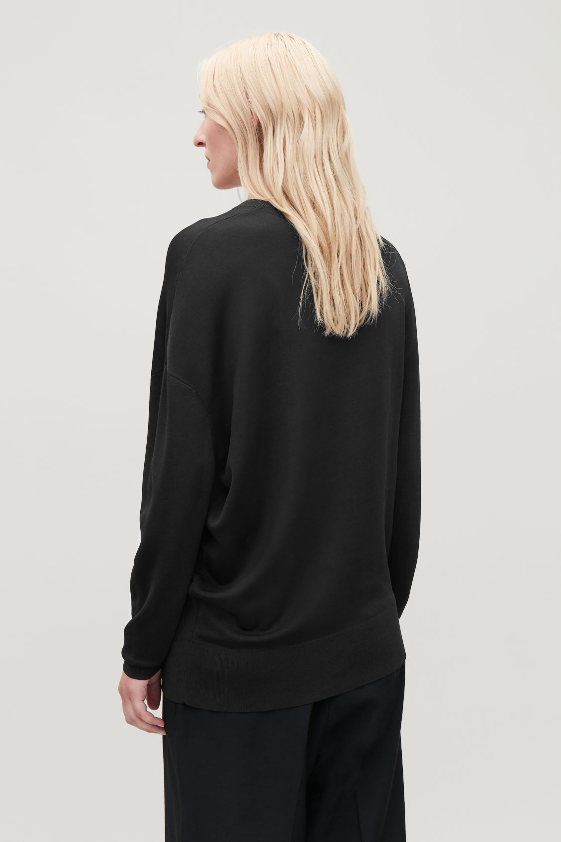 Model side image of Cos asymmetric draped knit jumper in black