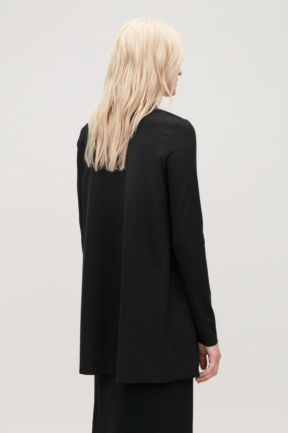 Model side image of Cos jersey top with draped neck in black