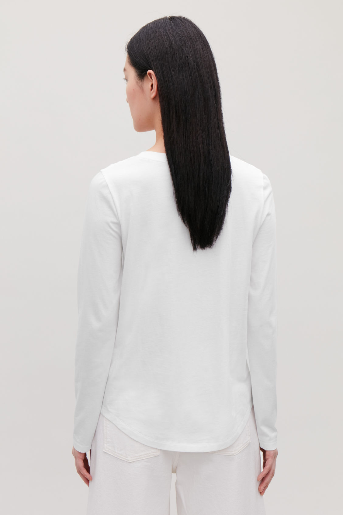 Model side image of Cos cotton long-sleeved top in white