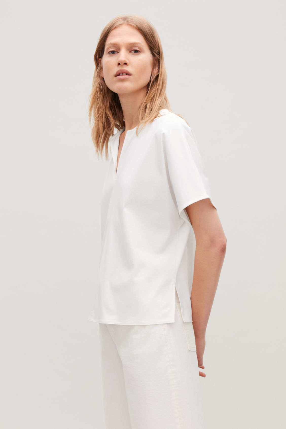 Model side image of Cos slit-neck jersey top in white