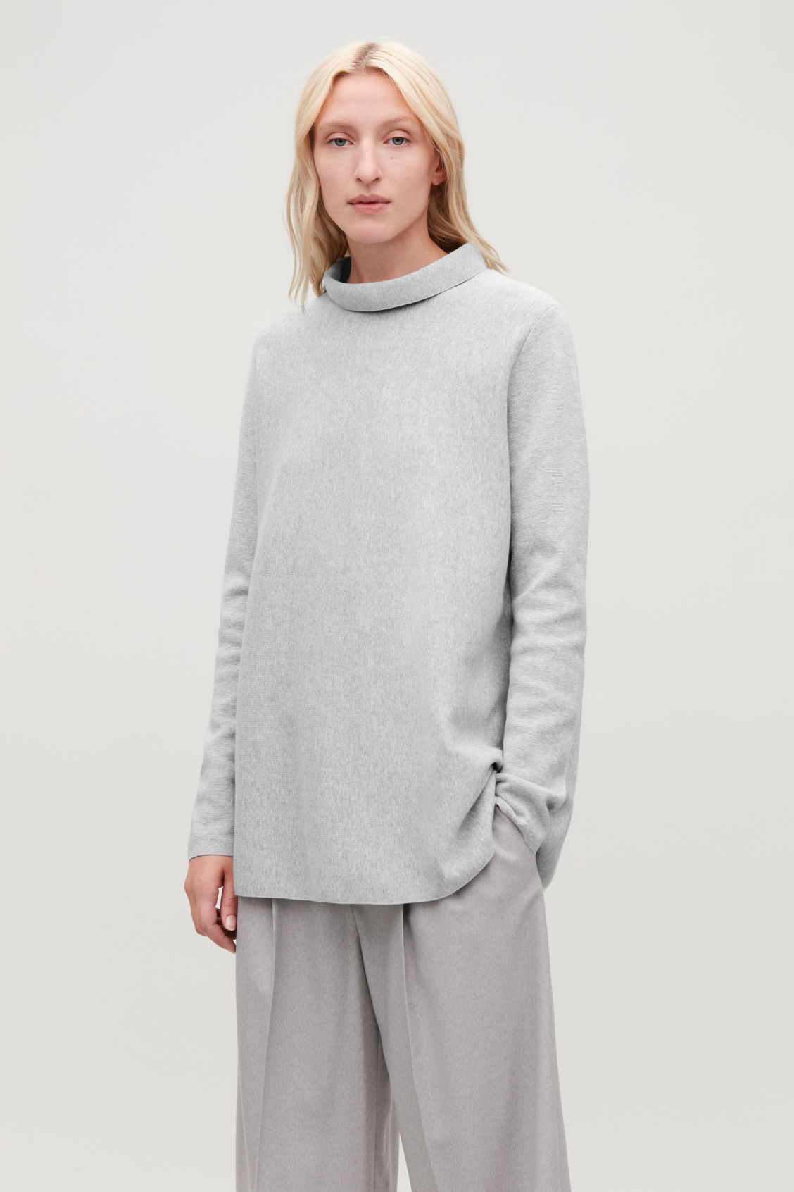 Model side image of Cos a-line top with funnel neck in grey