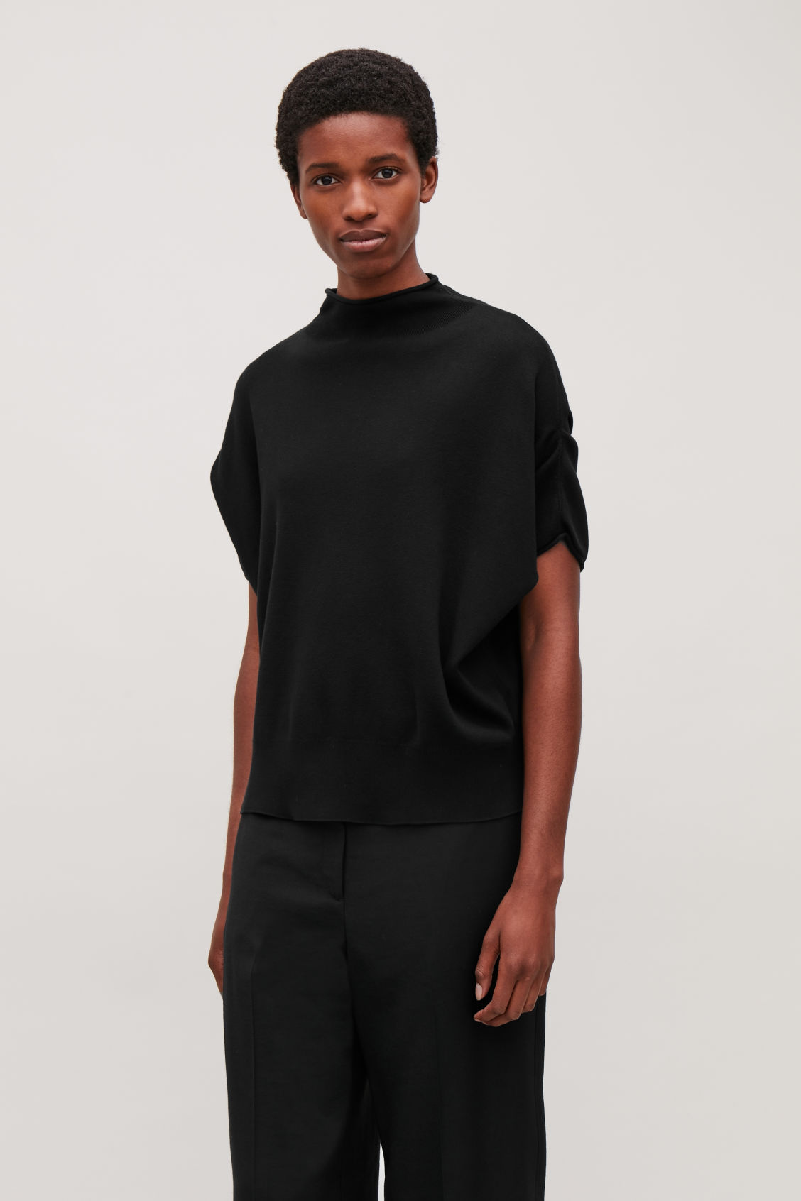 Model side image of Cos voluminous knitted top in black