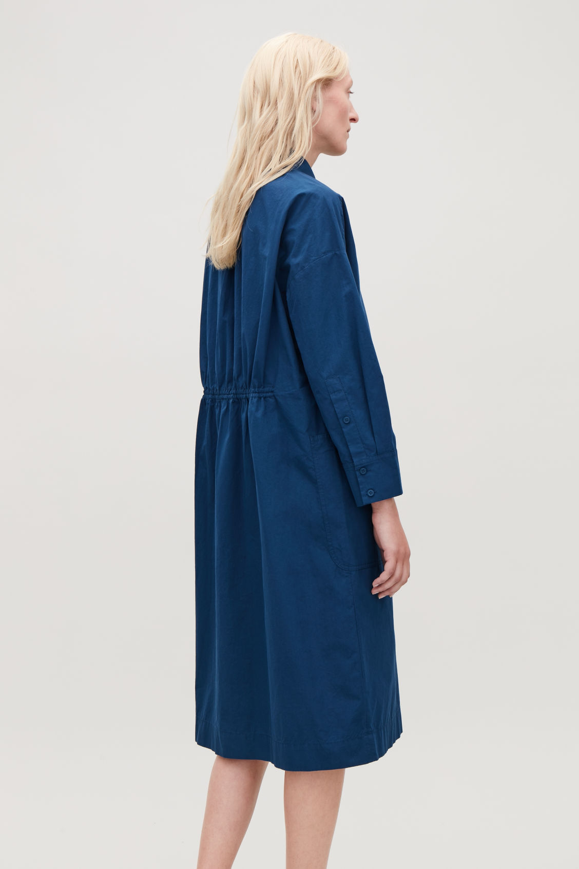 Model side image of Cos long jacket with gathered back in blue