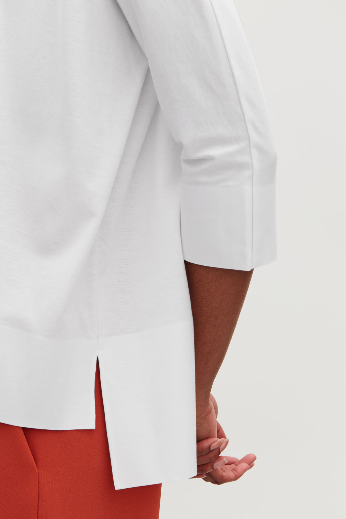 Model side image of Cos jersey top with bound details in white