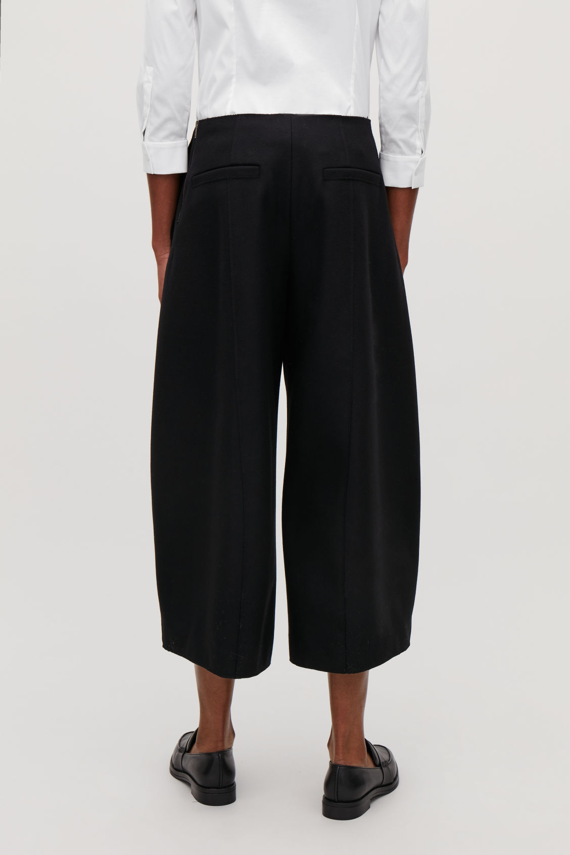 Model side image of Cos raw-cut rounded wool culottes in black