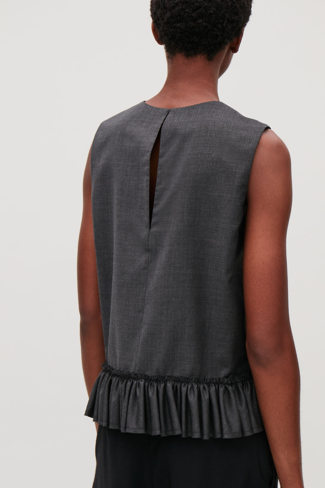 Model side image of Cos frill sleeveless wool top in grey