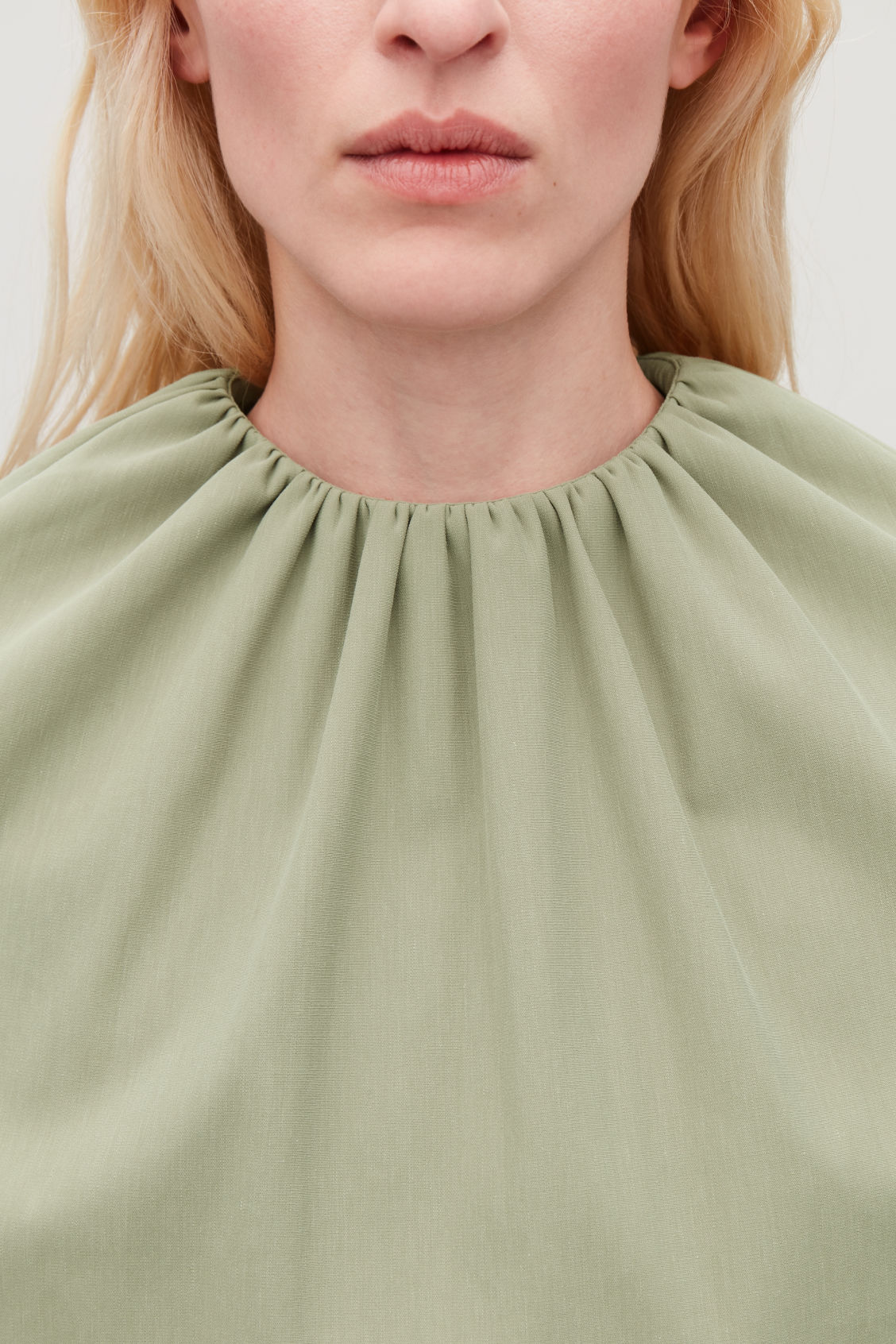 Model side image of Cos jersey top with cape layer in green