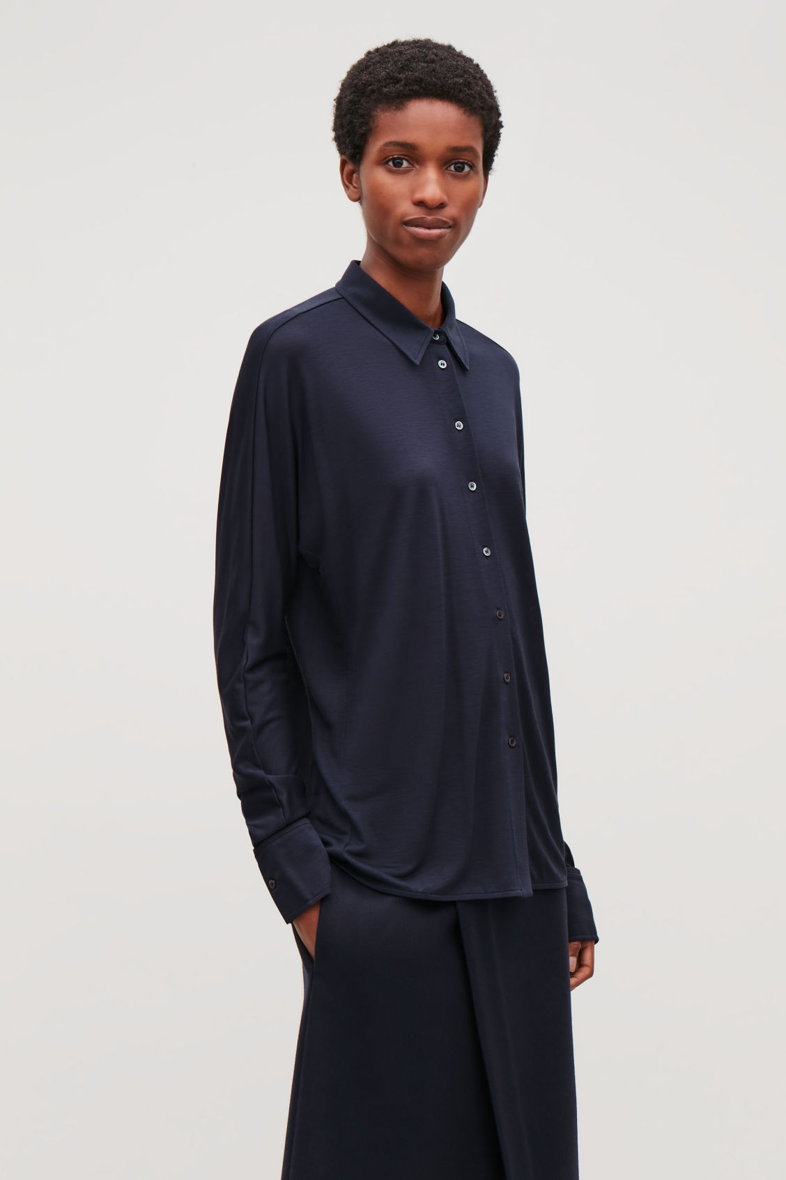 Model side image of Cos batwing-sleeved jersey shirt in blue