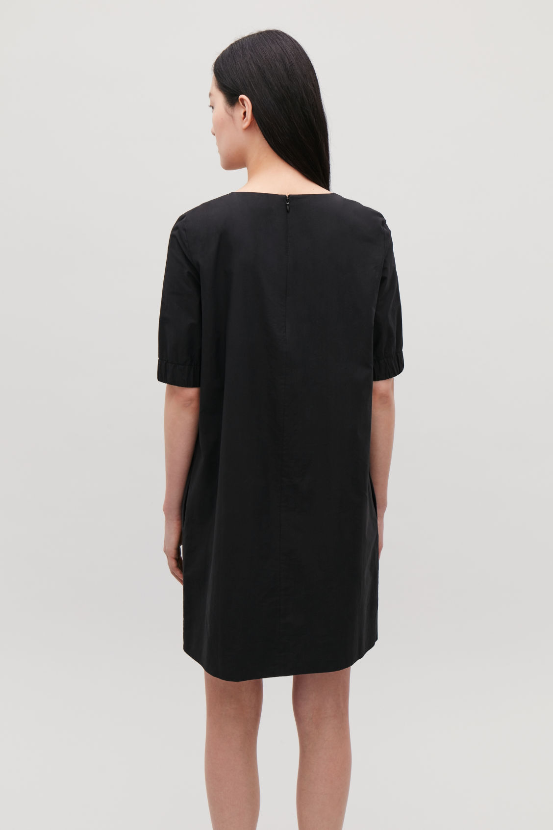 Model side image of Cos dress with elasticated sleeves in black