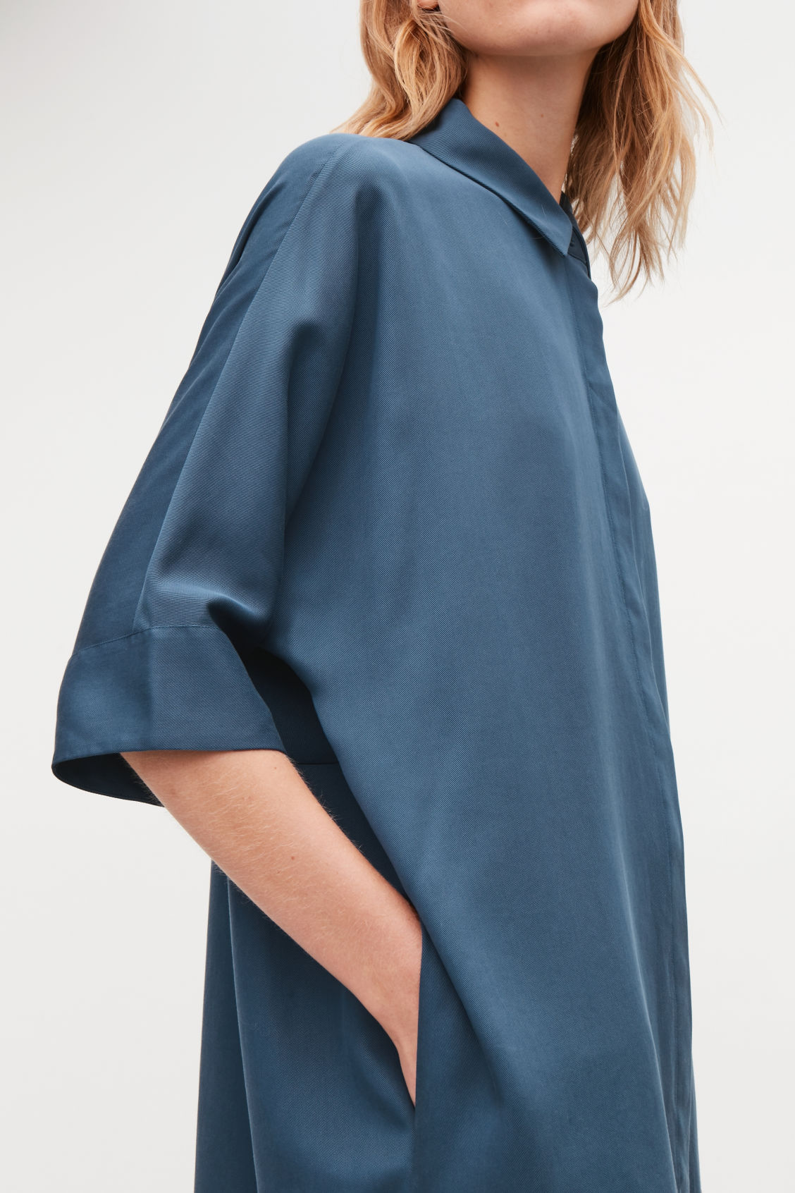 Model side image of Cos shirt dress with circle-cut back in blue