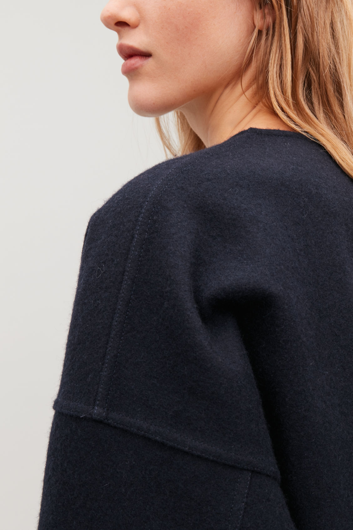 Model side image of Cos oversized boiled wool jacket in blue