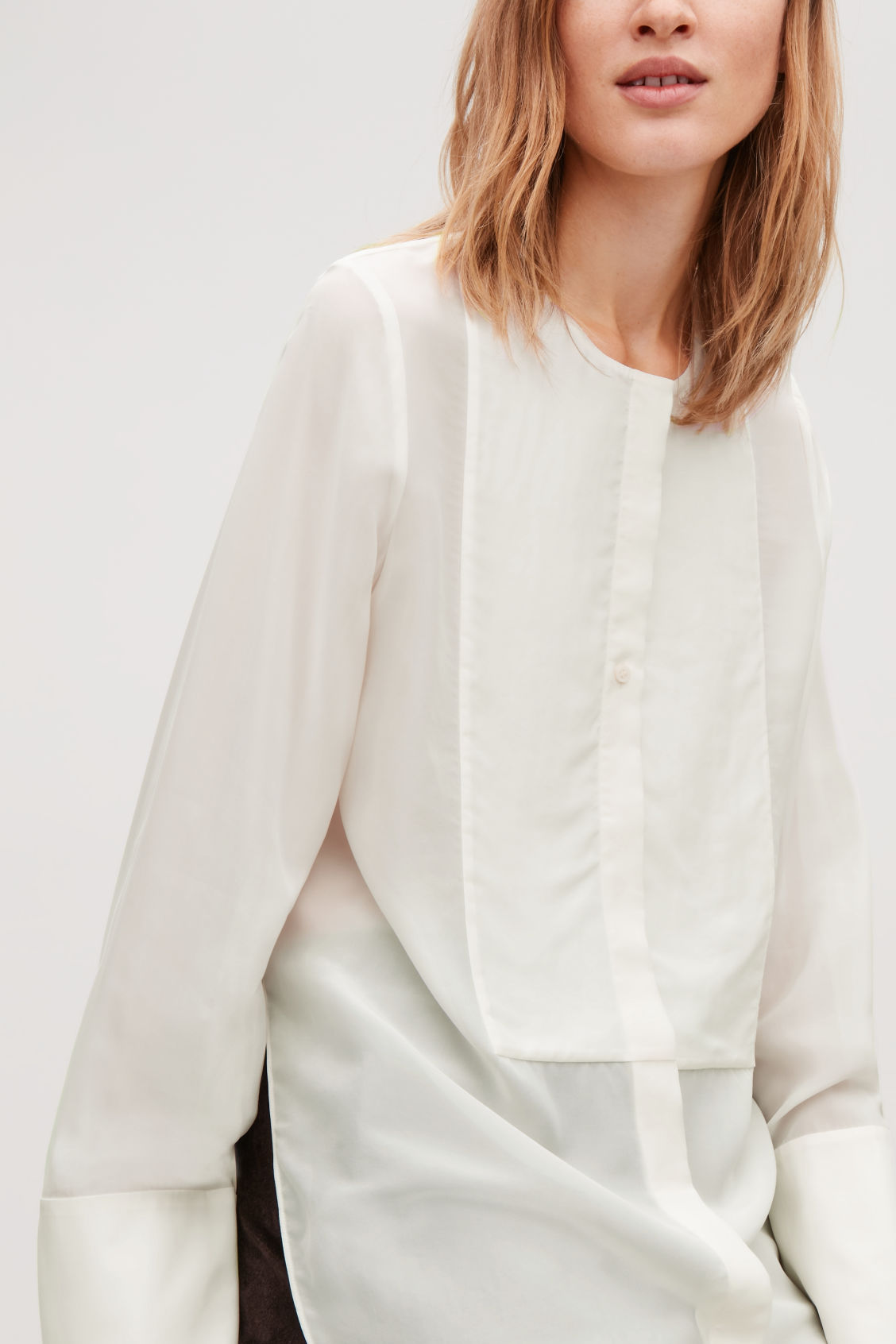 Model side image of Cos silk-blend shirt with bib front in neutral