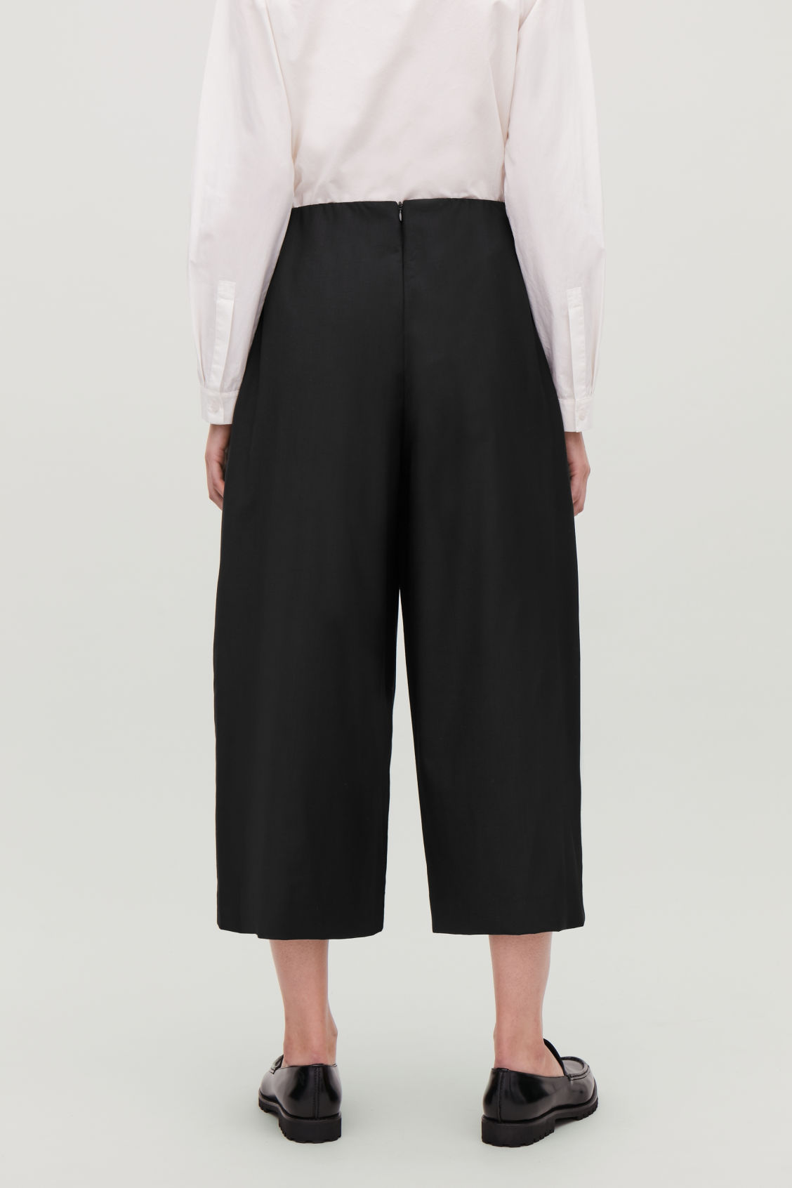 Model side image of Cos voluminous trousers in black