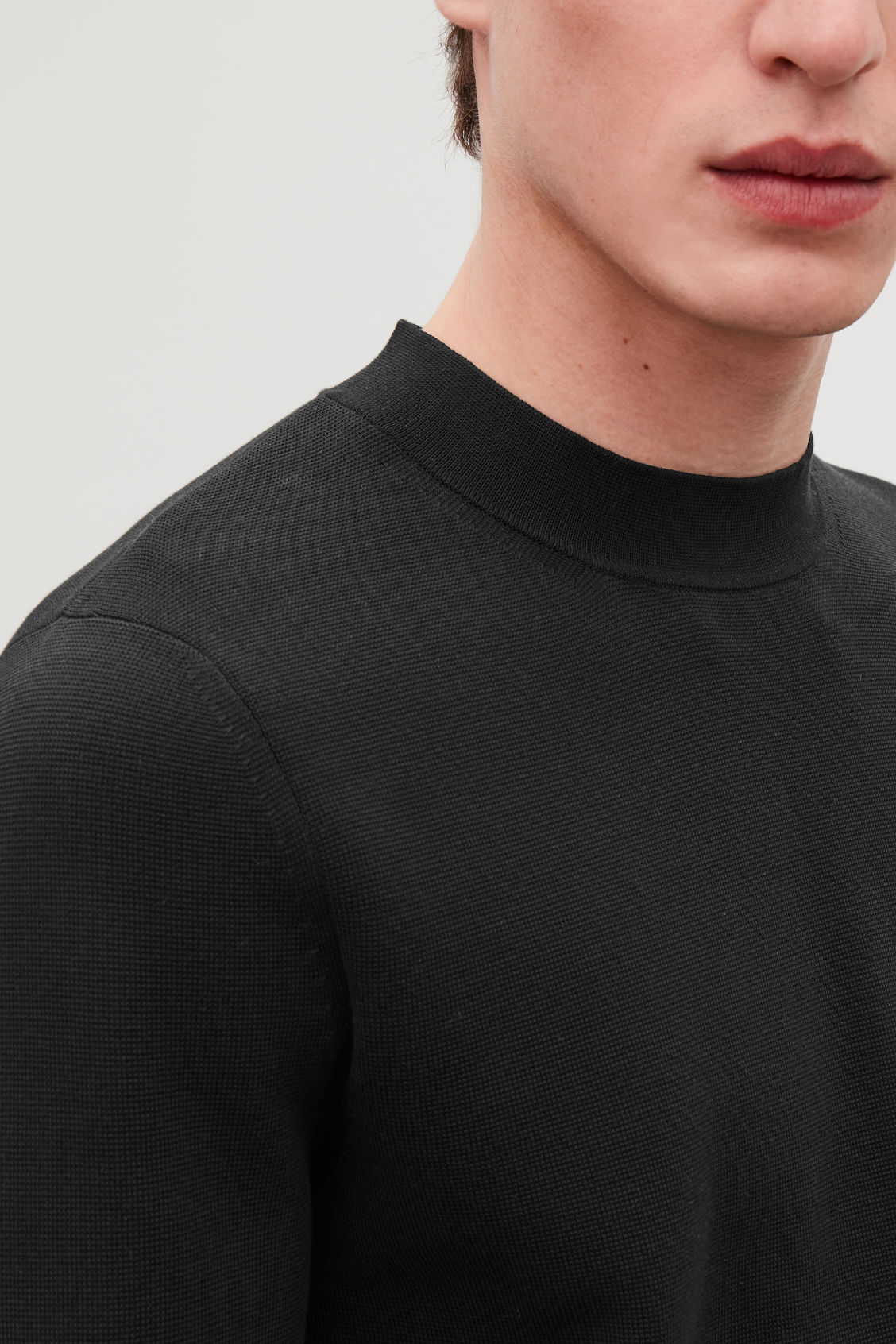 Model side image of Cos mock-neck knitted jumper in black