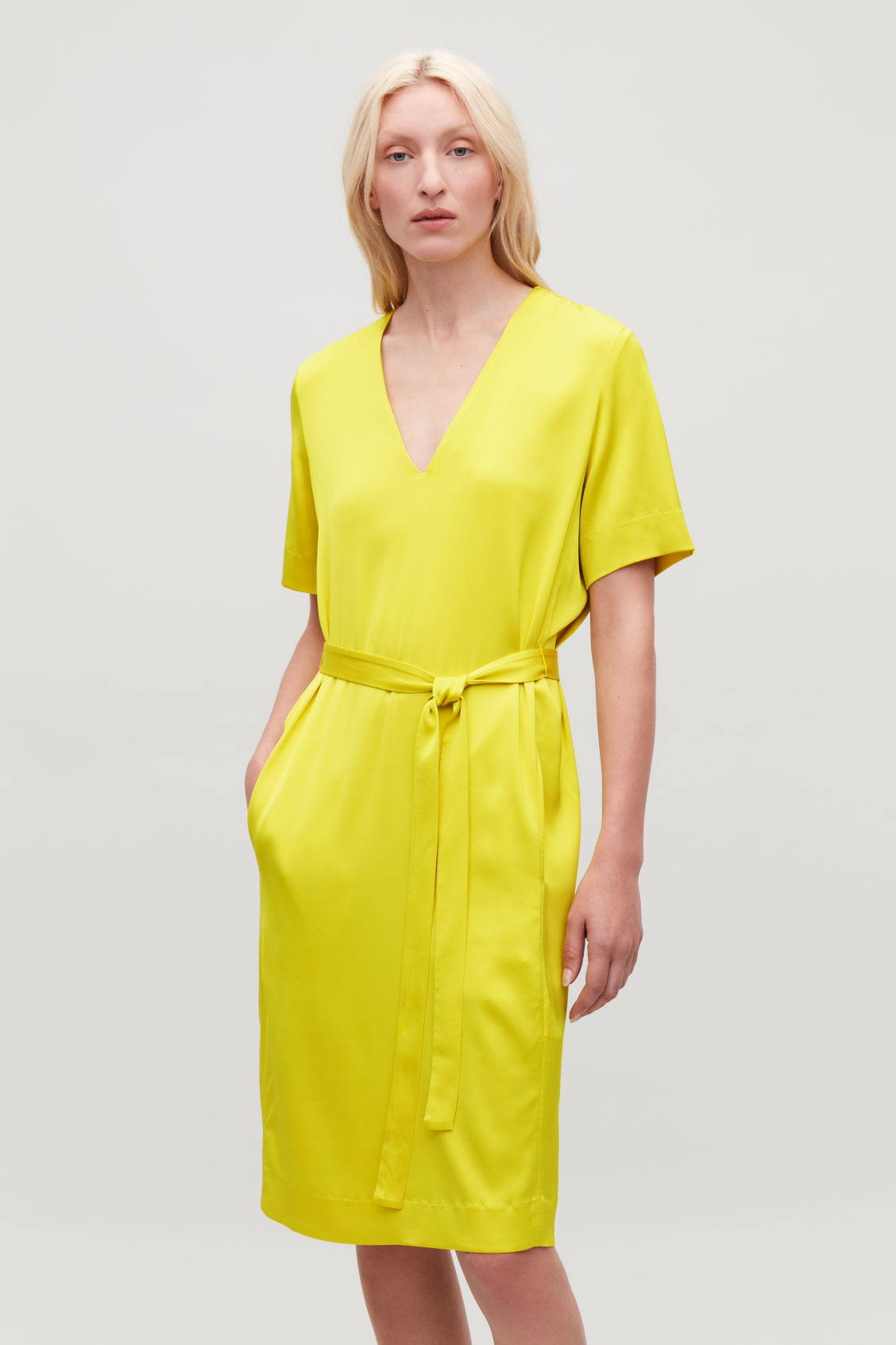 Model side image of Cos v-neck dress with belt in yellow