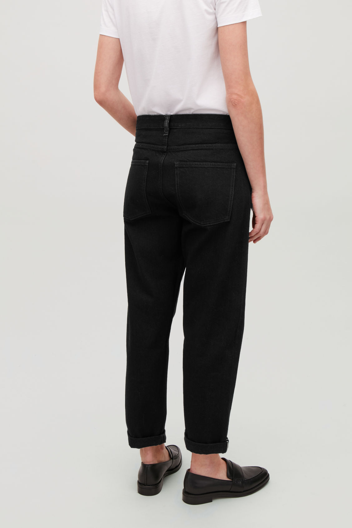 Model side image of Cos 28 inch selvedge relaxed leg jeans in black