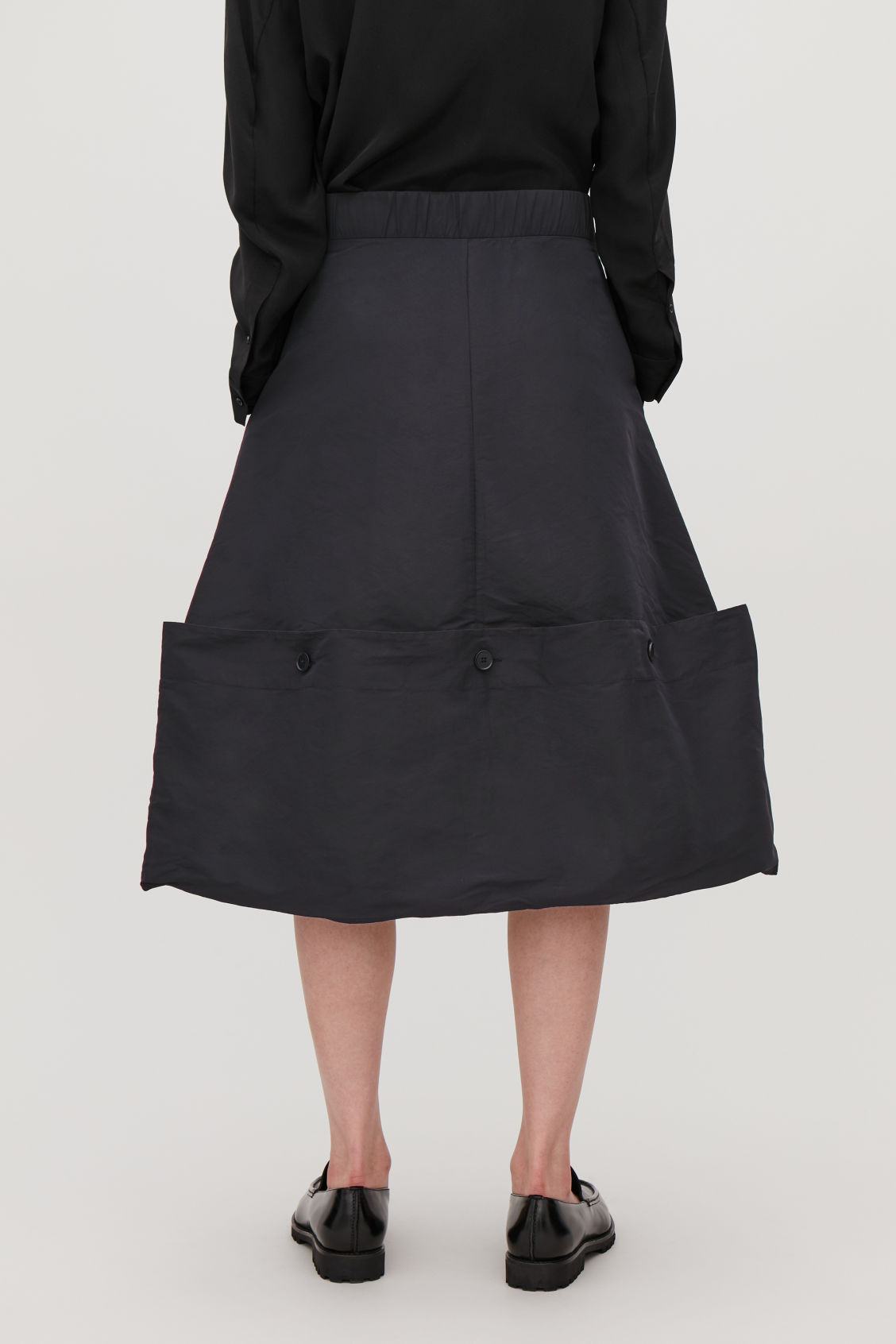 Model side image of Cos draped skirt with buttons in blue