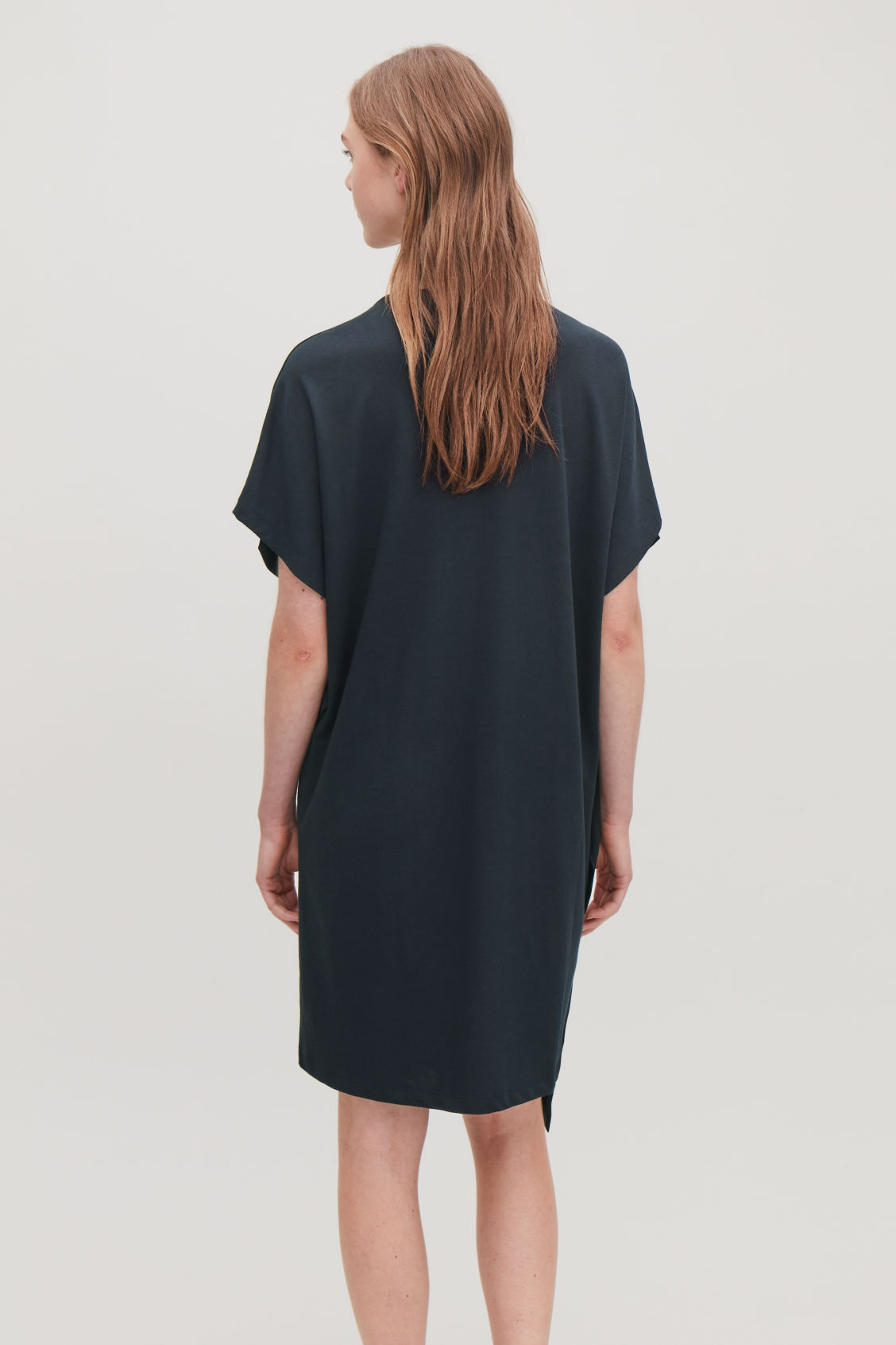 Model side image of Cos dress with topstitches in blue