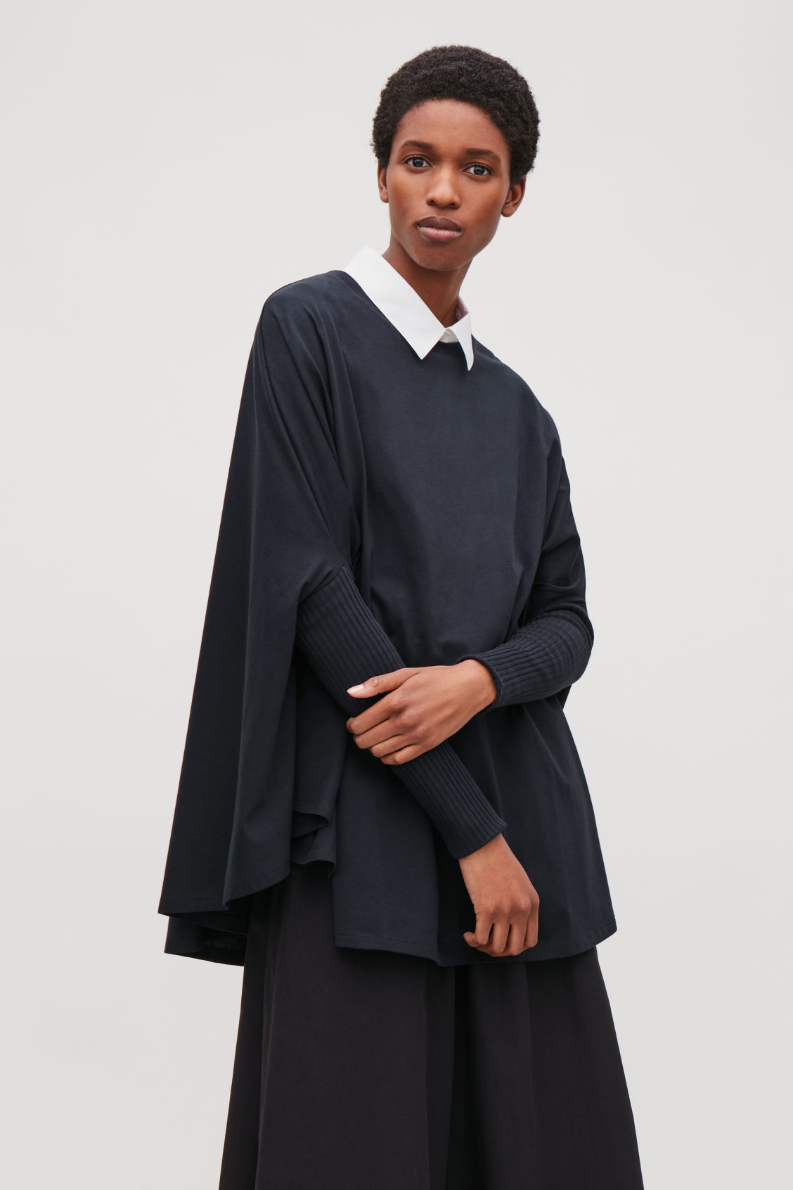 Model side image of Cos circle-cut top with rib sleeves in blue