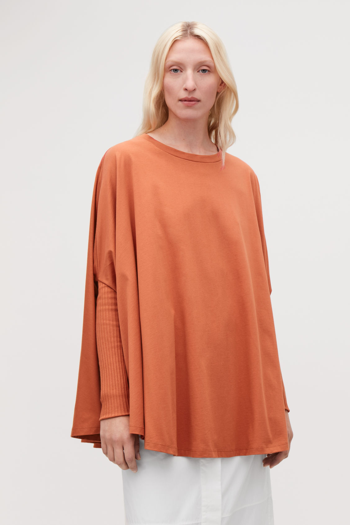 Model side image of Cos circle-cut top with rib sleeves in orange
