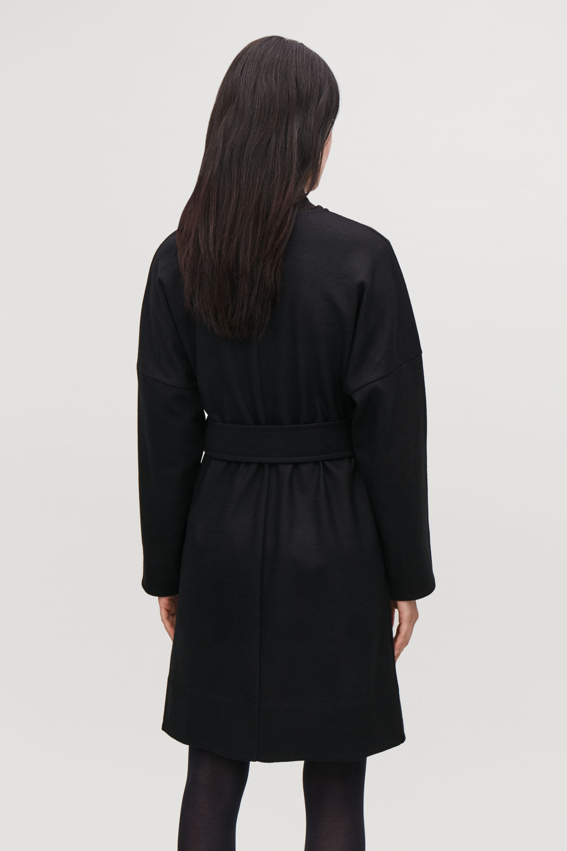 Model side image of Cos belted wool wrap dress in black