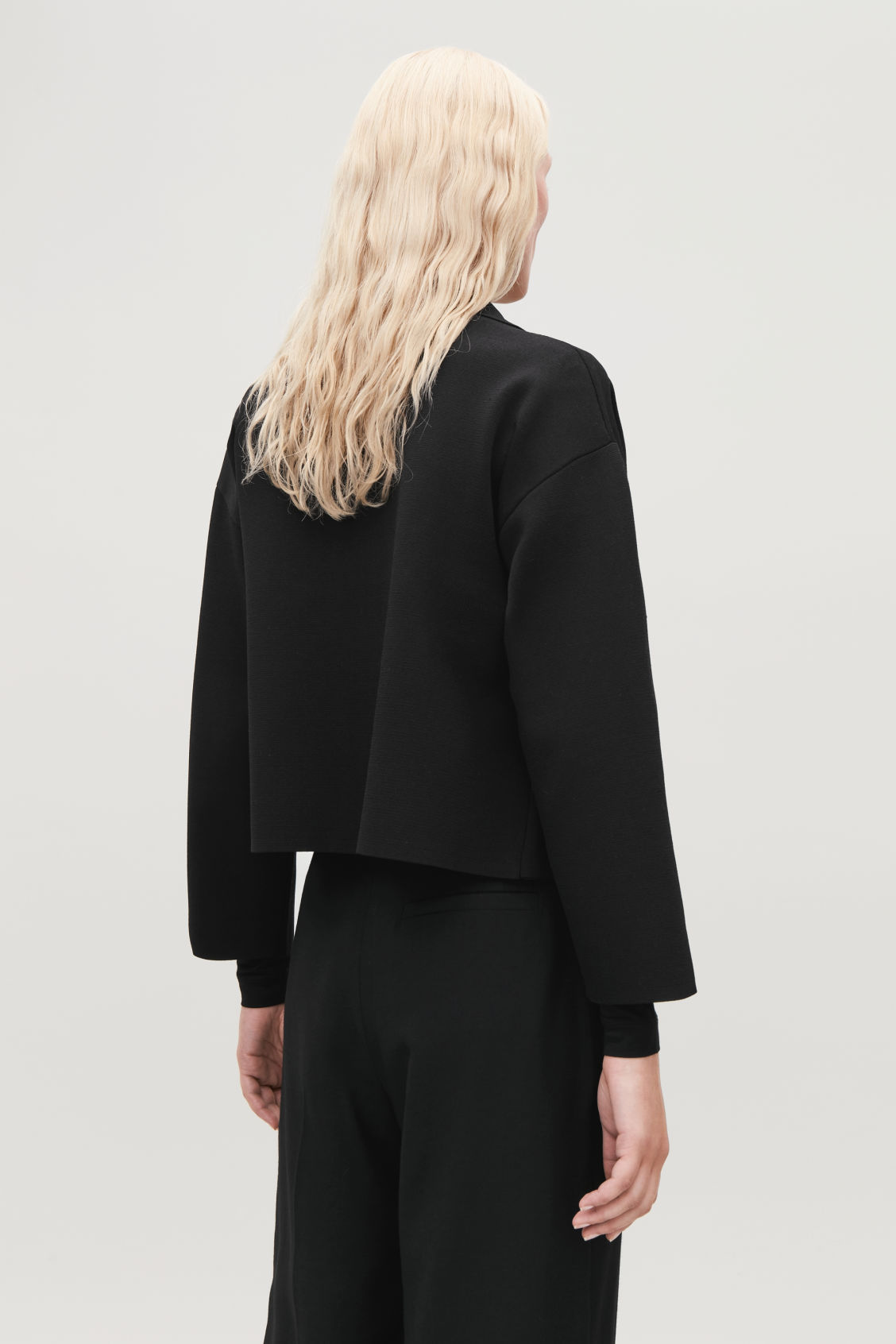 Model side image of Cos knitted jacket with pocket in black