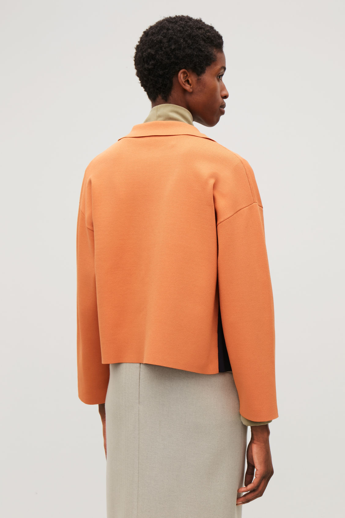 Model side image of Cos knitted jacket with pocket in orange