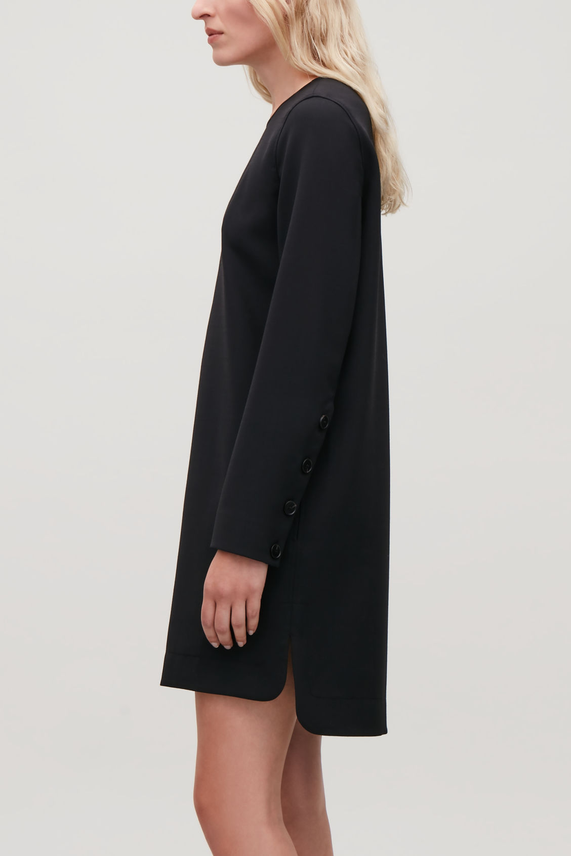 Model side image of Cos short dress with buttoned sleeves in black