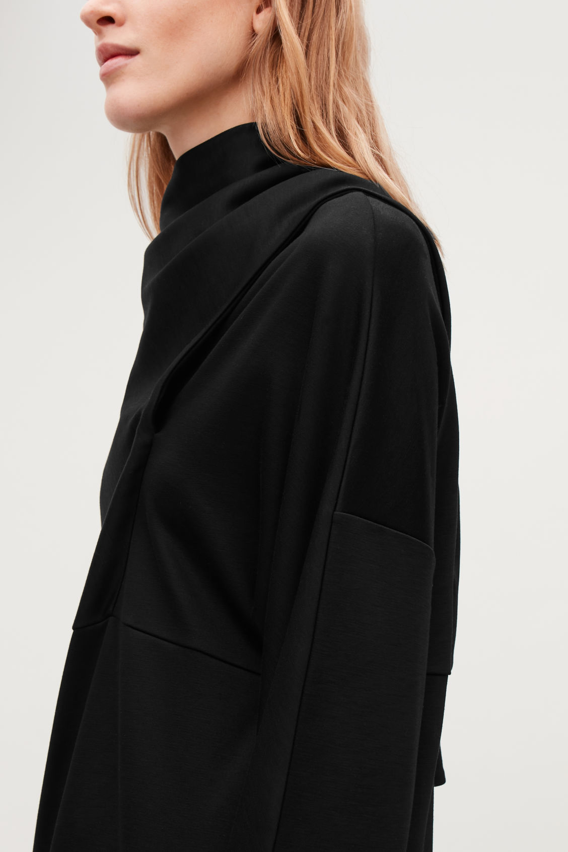Model side image of Cos jersey dress with draped ties in black
