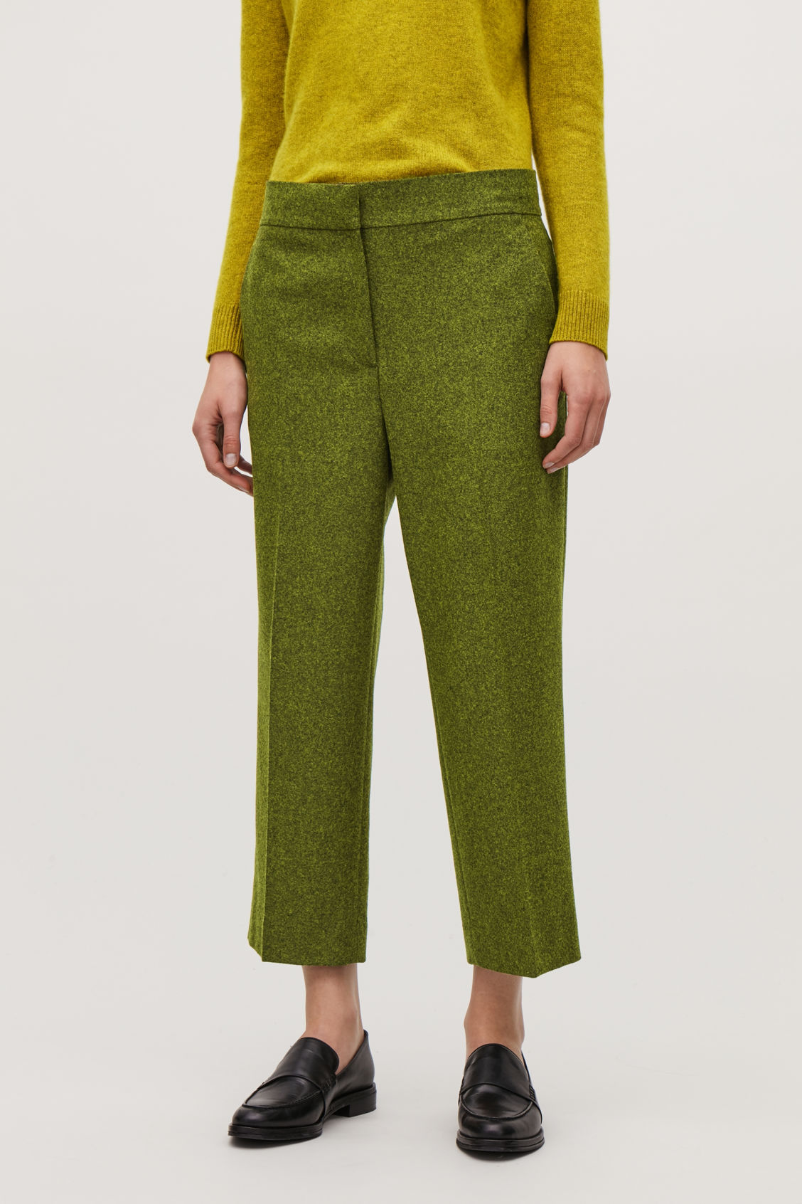 Model side image of Cos cropped melange-wool trousers in green