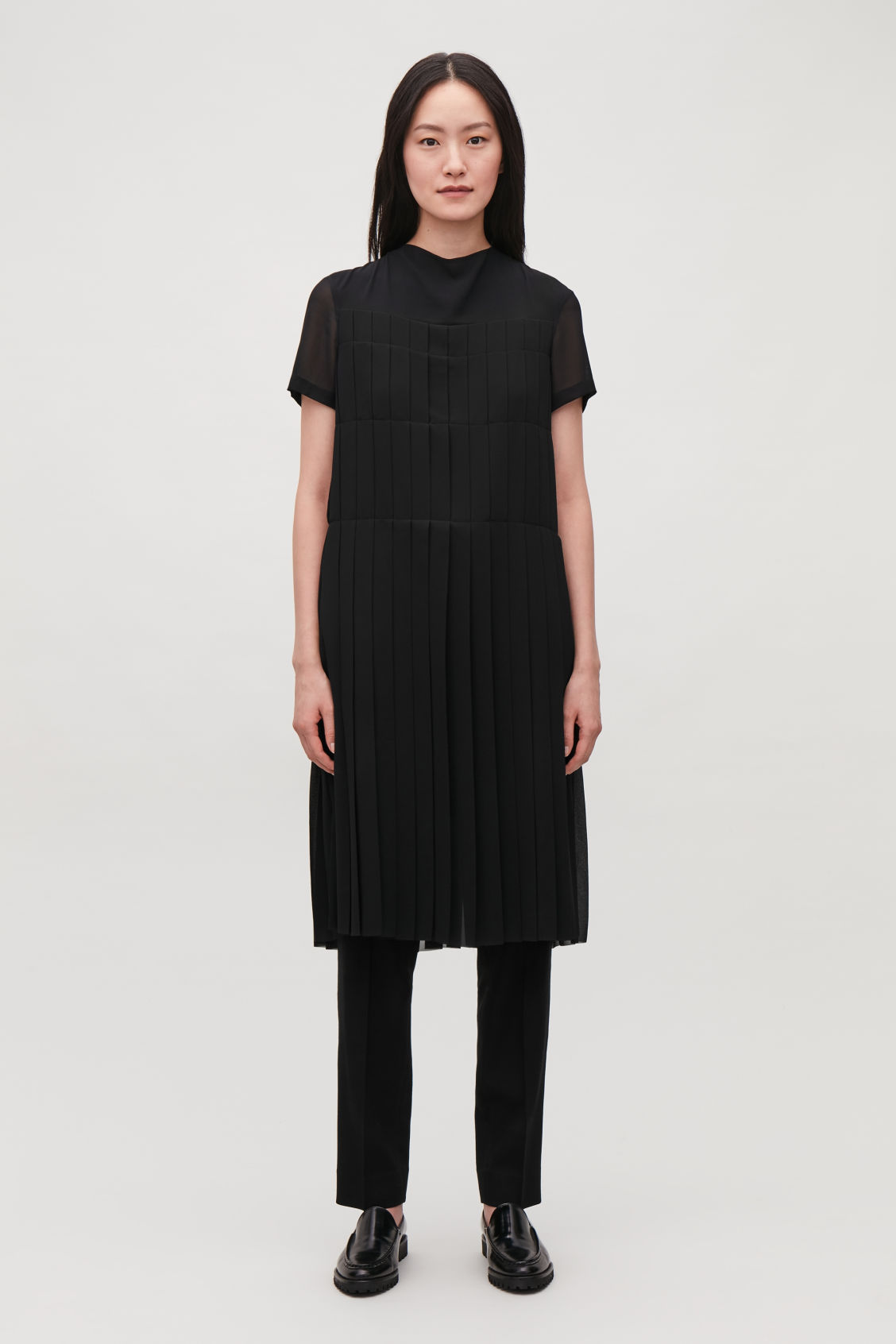 Model side image of Cos draped-neck pleated dress in black