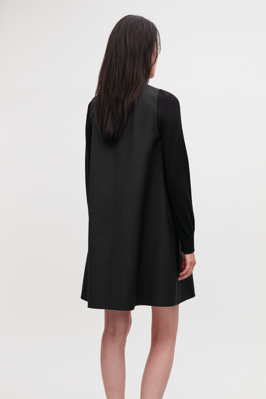 Model side image of Cos tailored wool a-line dress in black