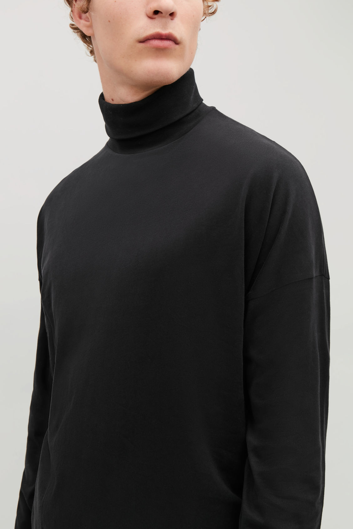 Model side image of Cos cotton roll-neck  jumper in black