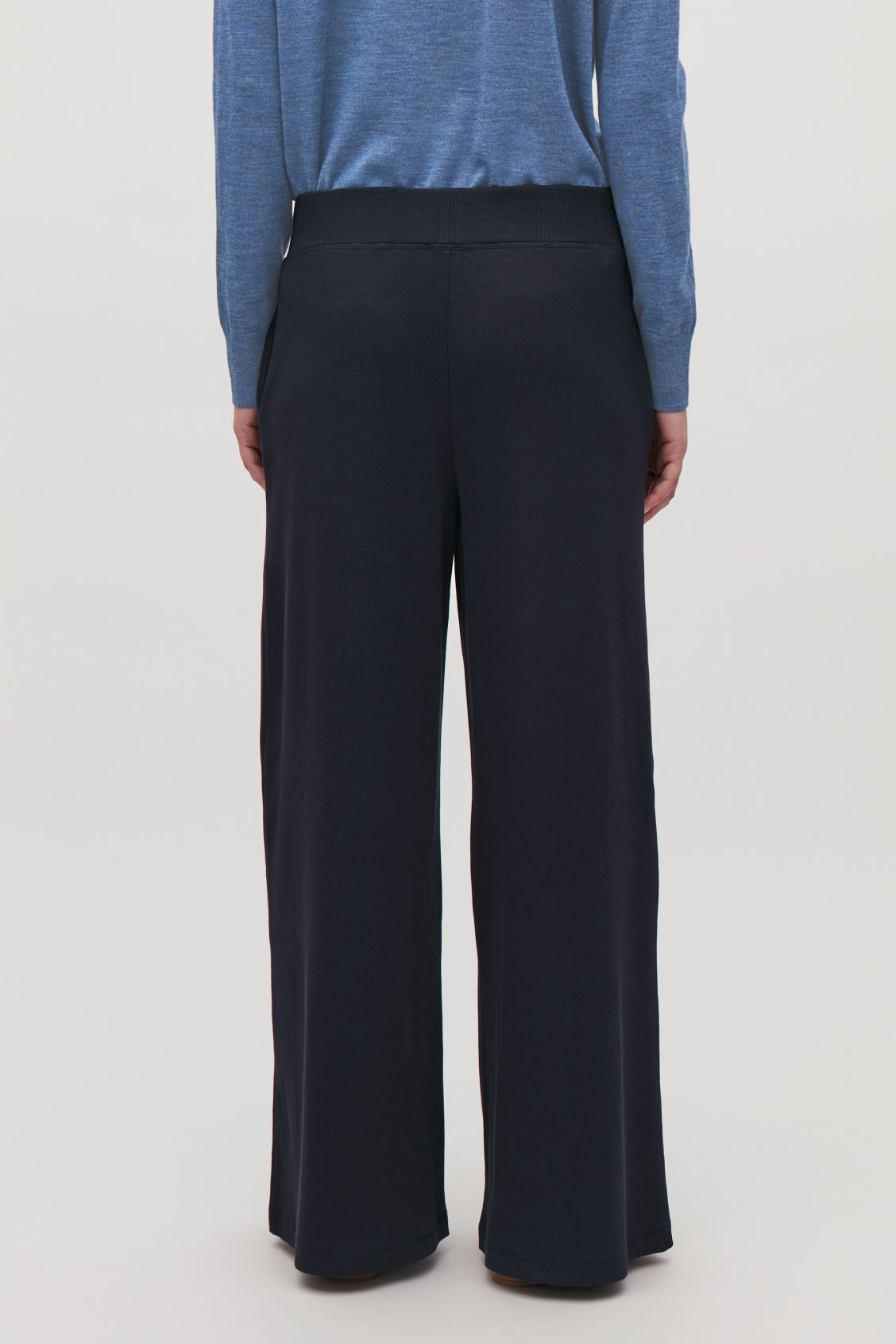 Model side image of Cos wide ribbed-jersey trousers in blue