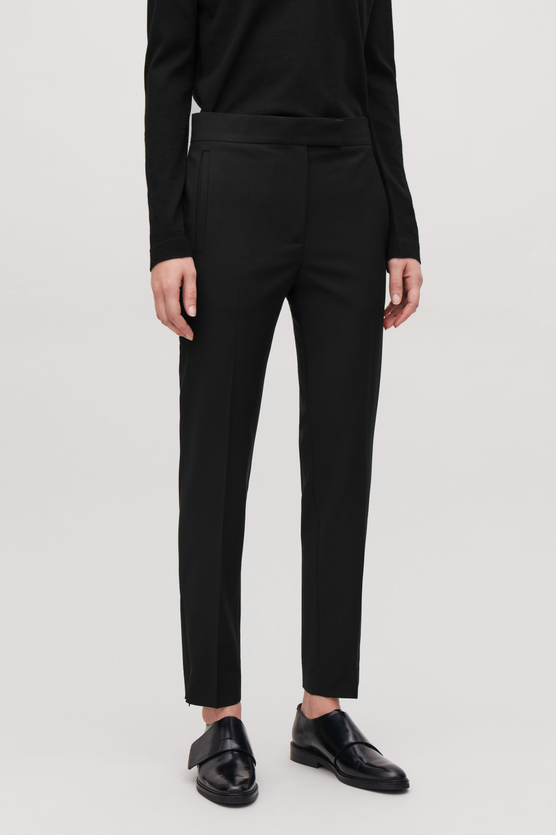 Model side image of Cos slim tailored trousers with zips in black