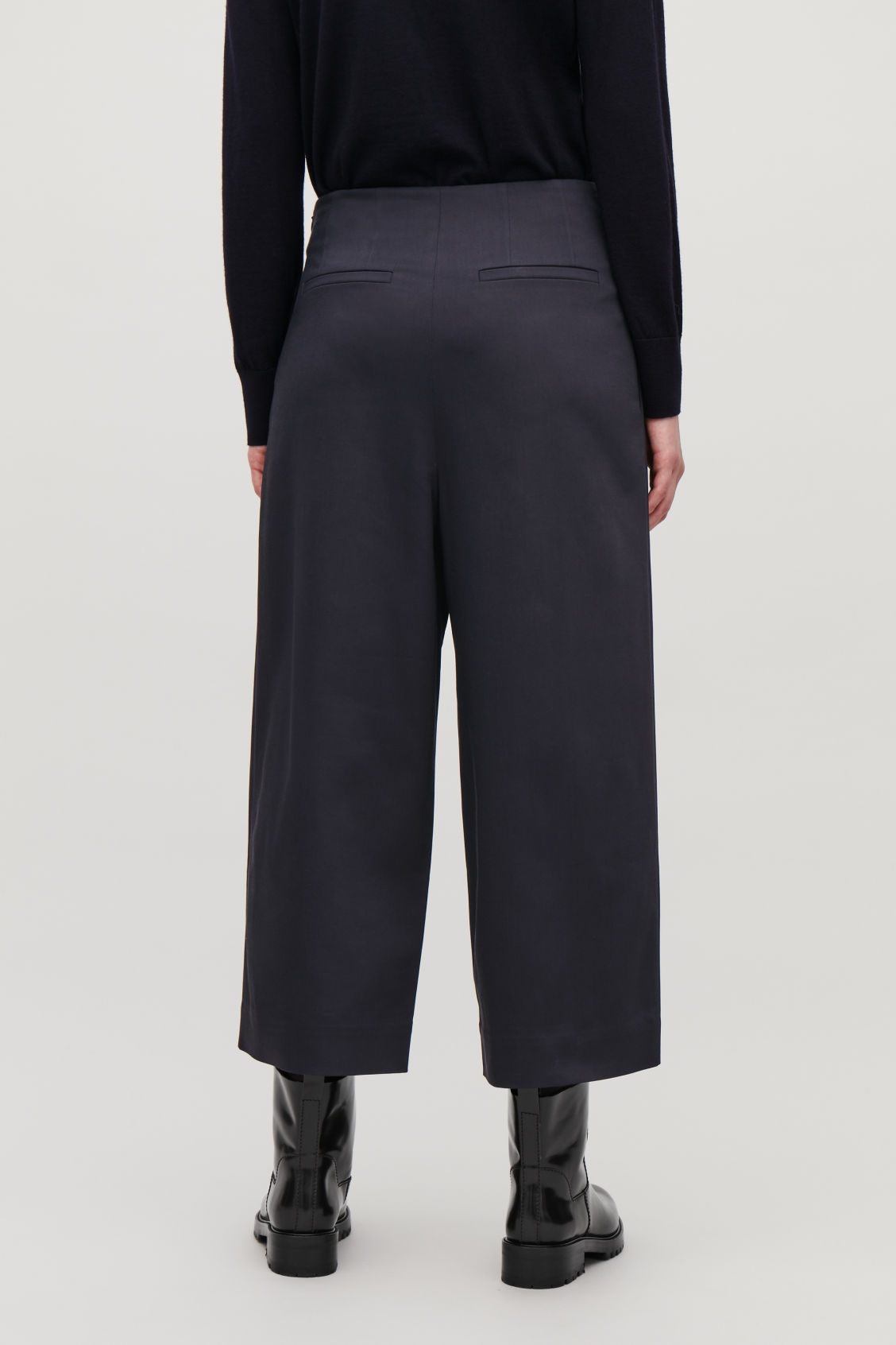 Model side image of Cos stretch-cotton pleated trousers in blue