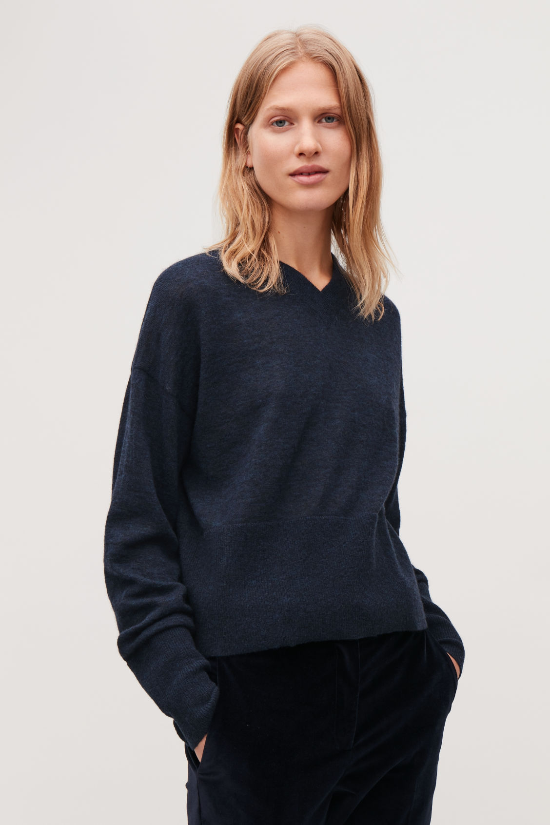 Model side image of Cos boxy wool v-neck jumper in blue