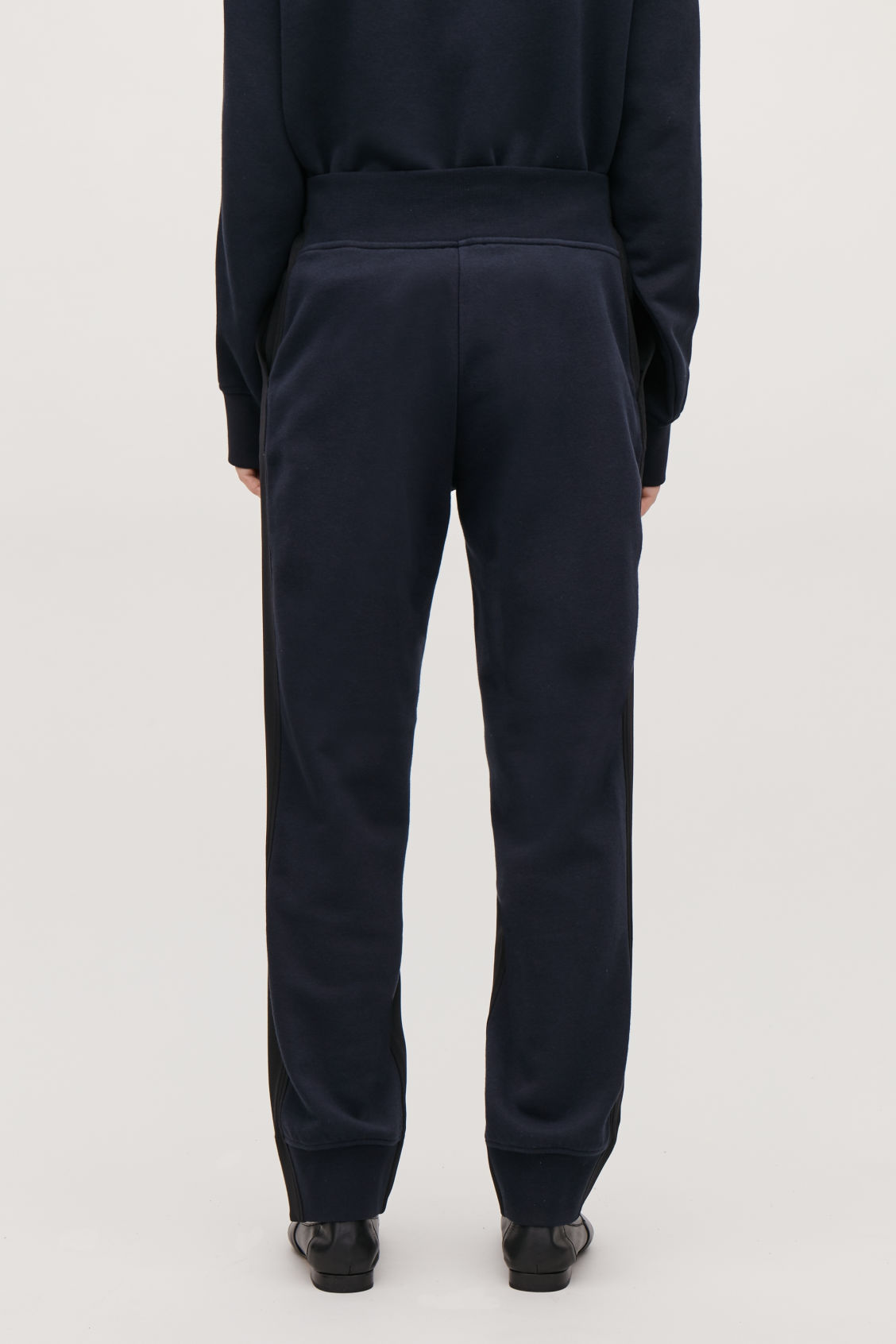 Model side image of Cos woven-jersey mix trousers in black