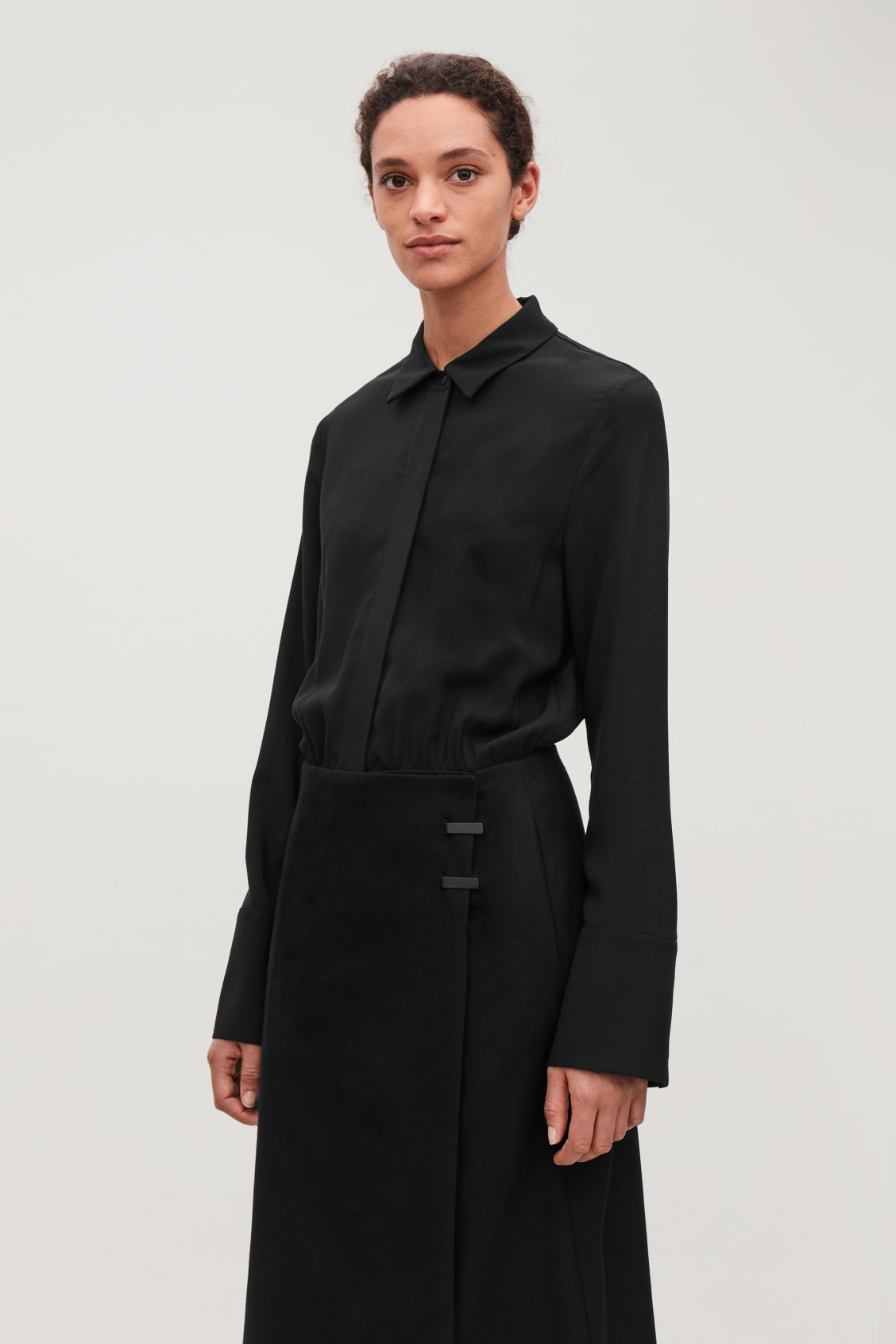 Model side image of Cos long coat dress in black
