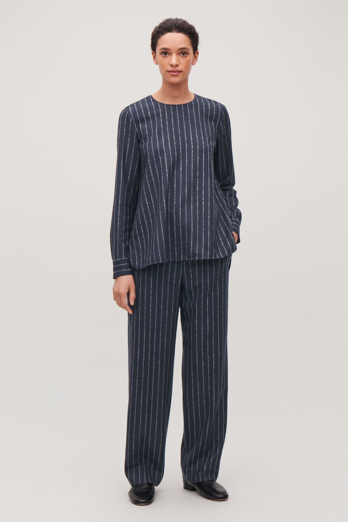 Model side image of Cos pinstriped wide wool trousers in blue