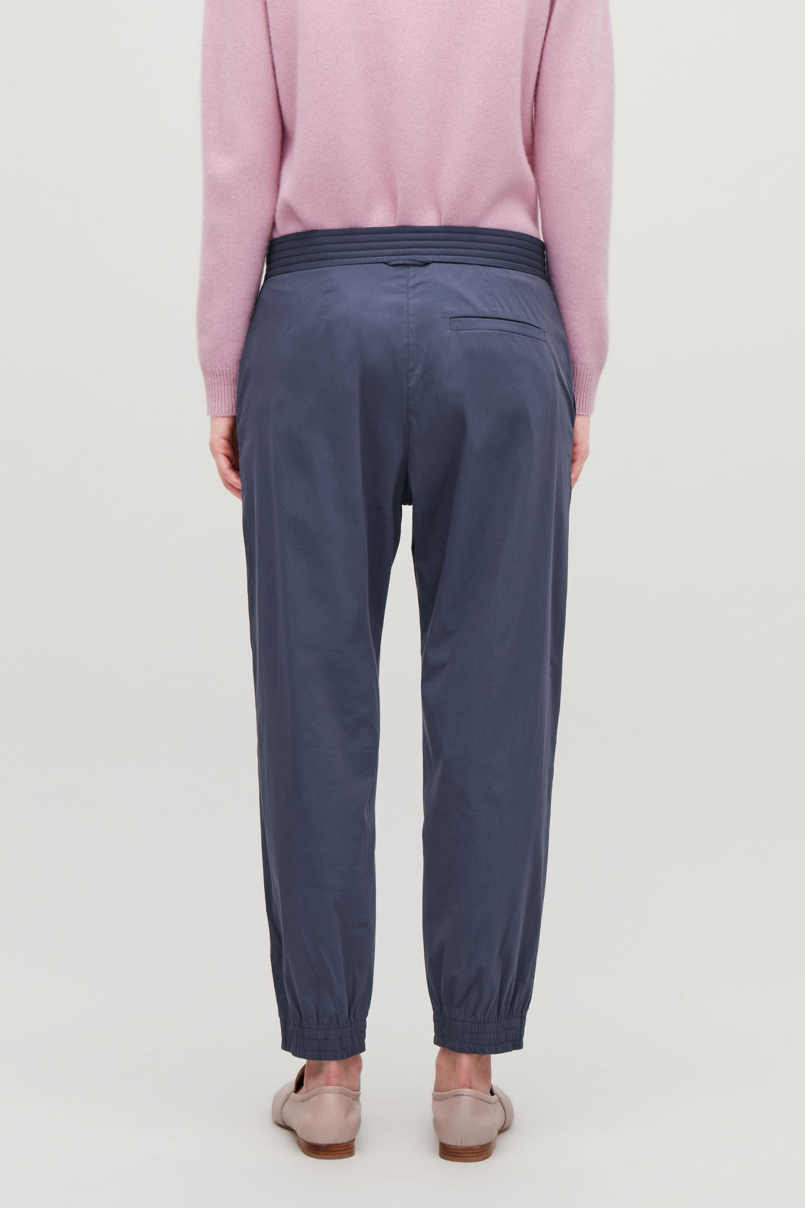 Model side image of Cos padded-waist cotton trousers in blue