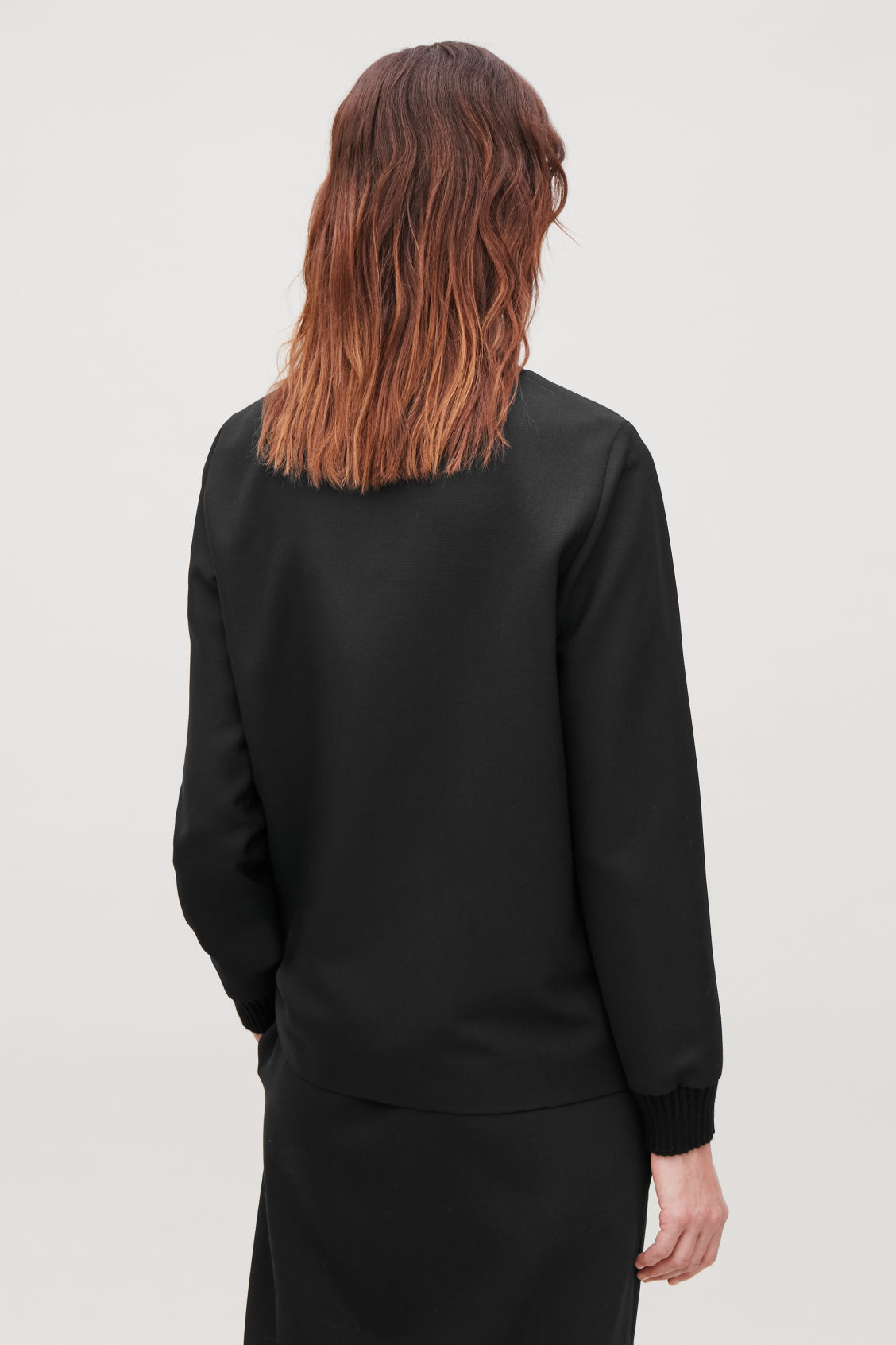 Model side image of Cos top with knitted edges in black