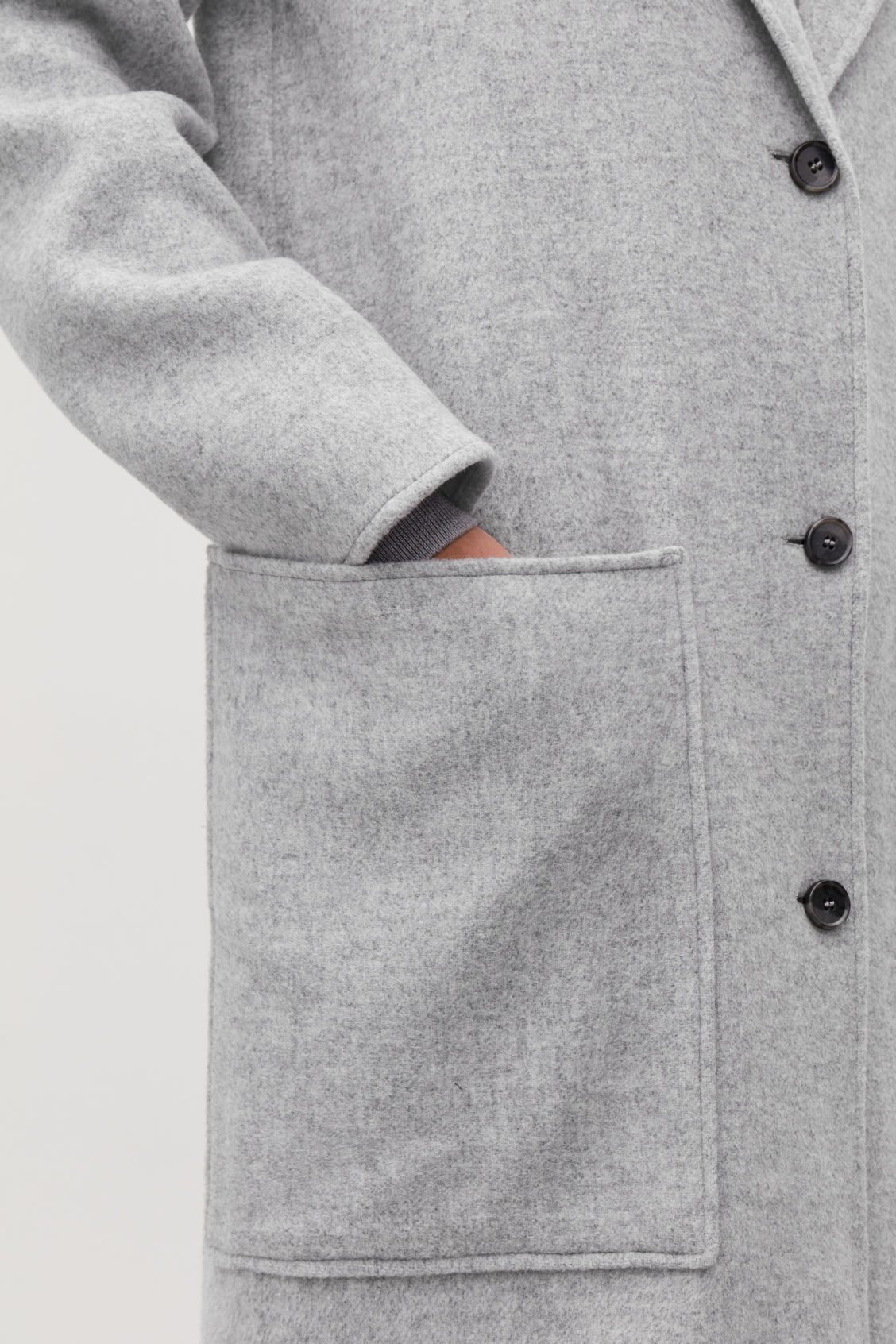 Model side image of Cos wool coat with large pockets in grey