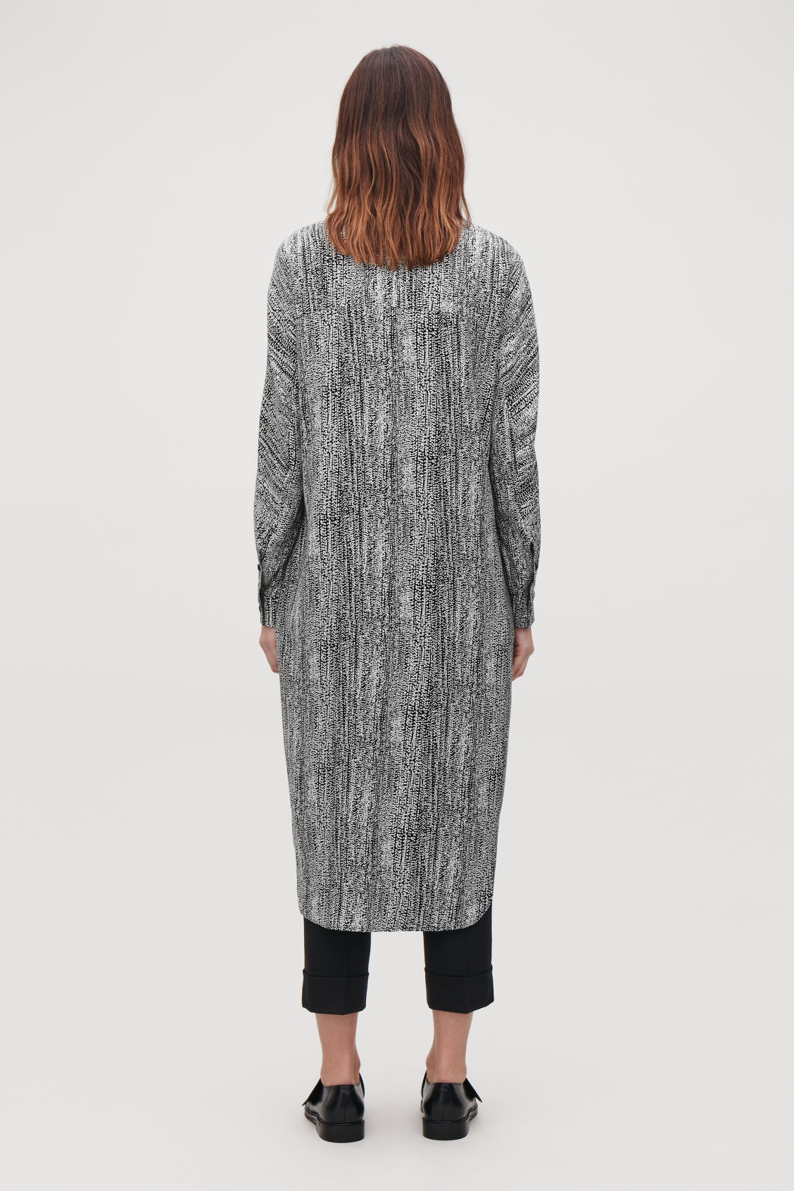 Model side image of Cos printed mid-length dress in black