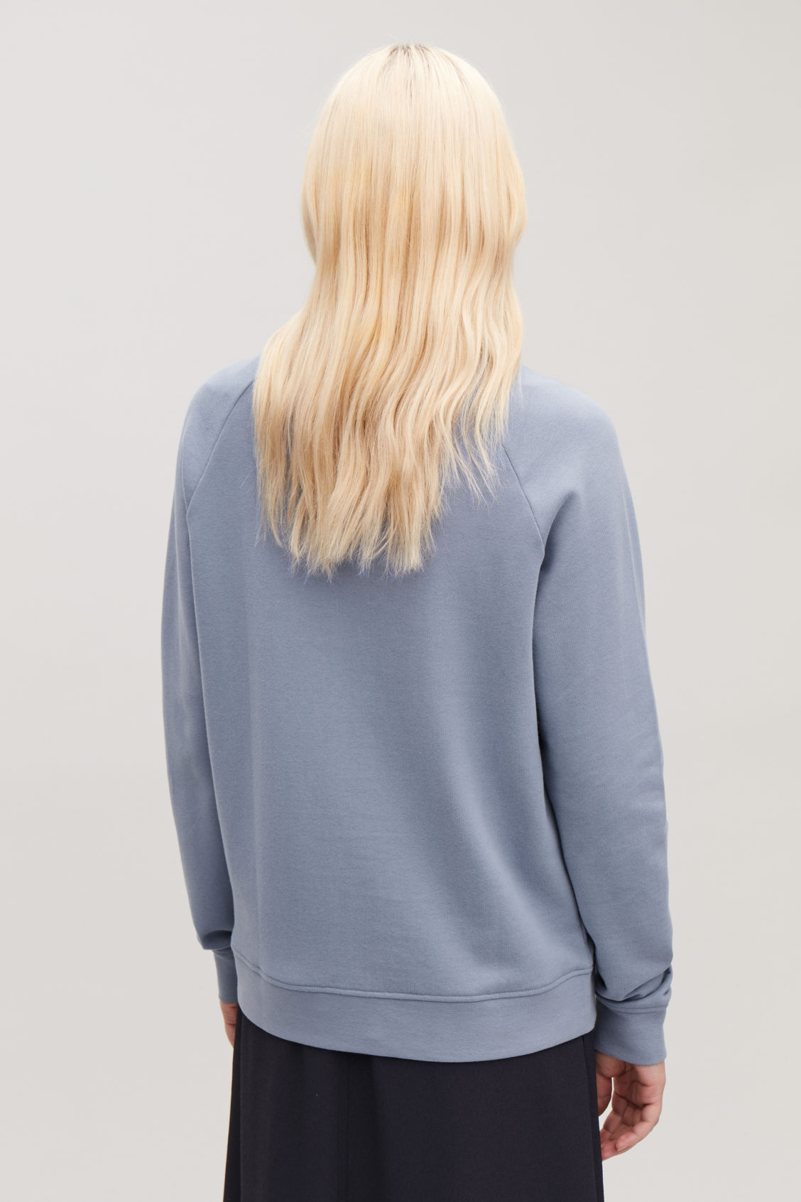 Model side image of Cos relaxed jersey sweatshirt in blue