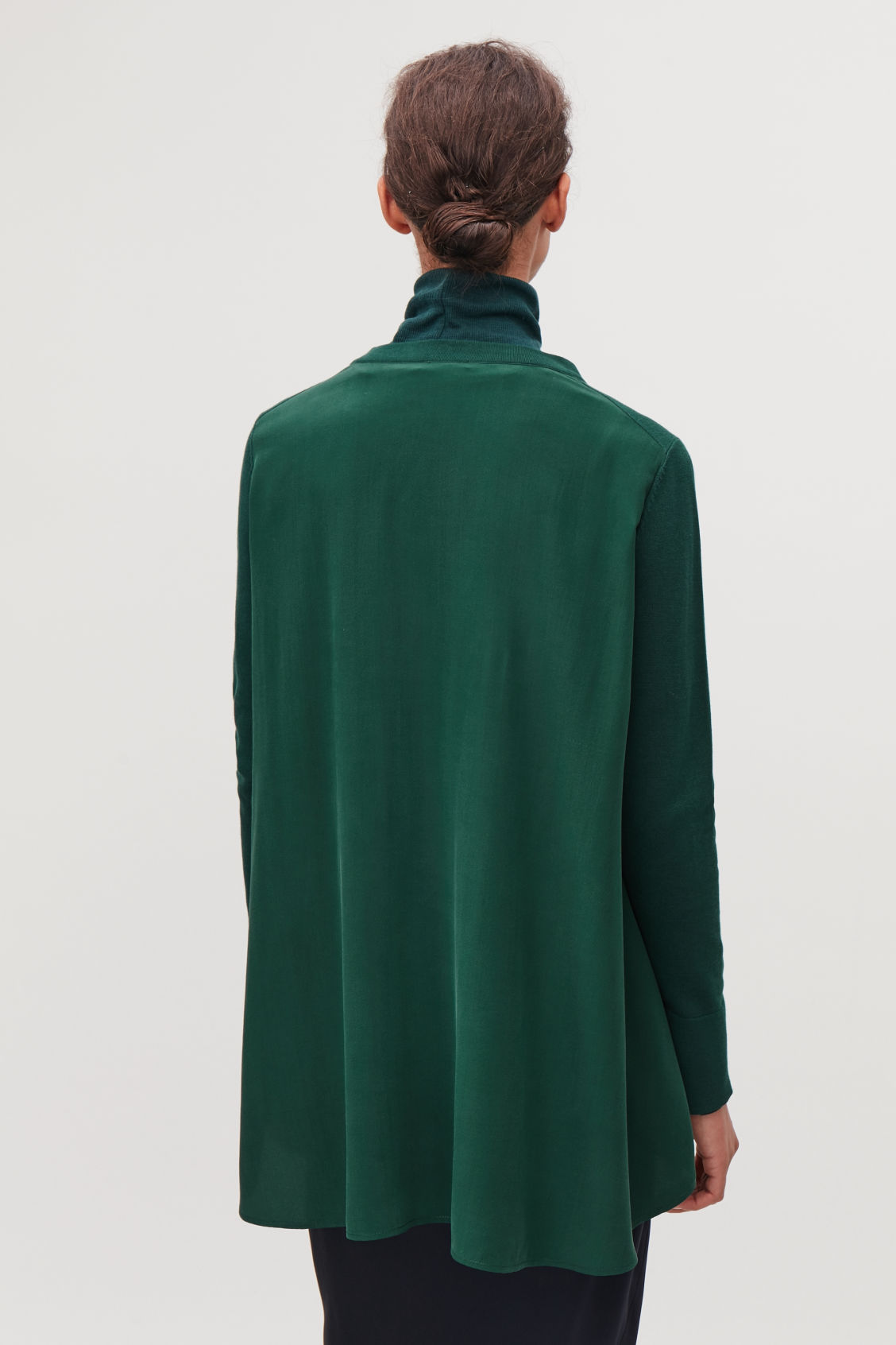 Model side image of Cos knit top with silk panel in green
