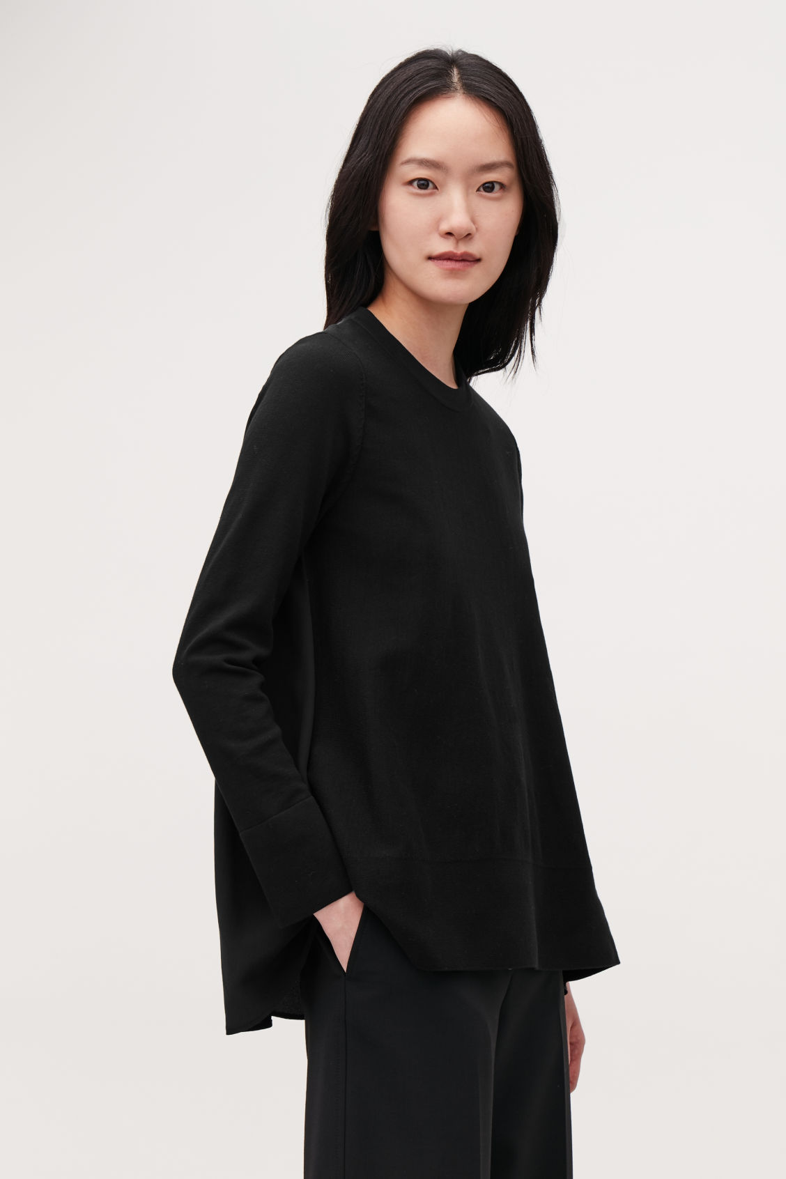 Model side image of Cos knit top with silk panel in black