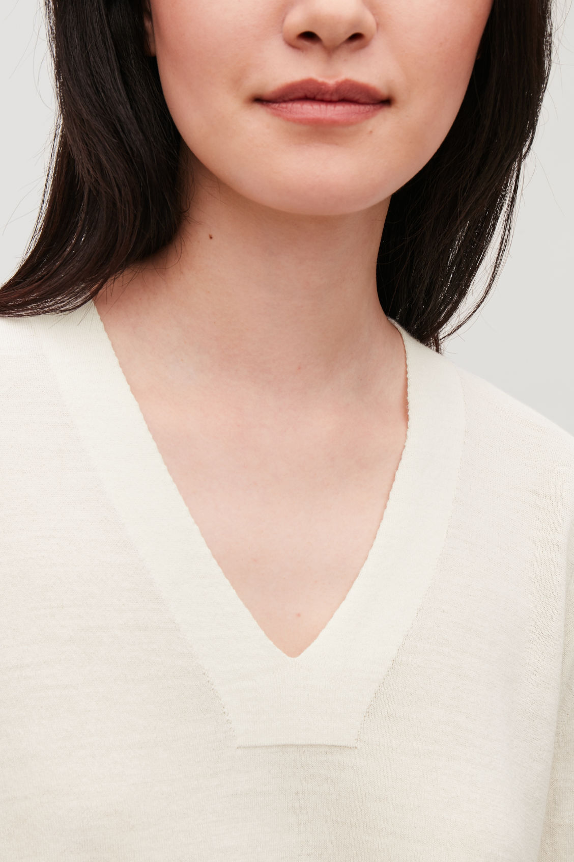 Model side image of Cos merino jumper with deep v-neck in white