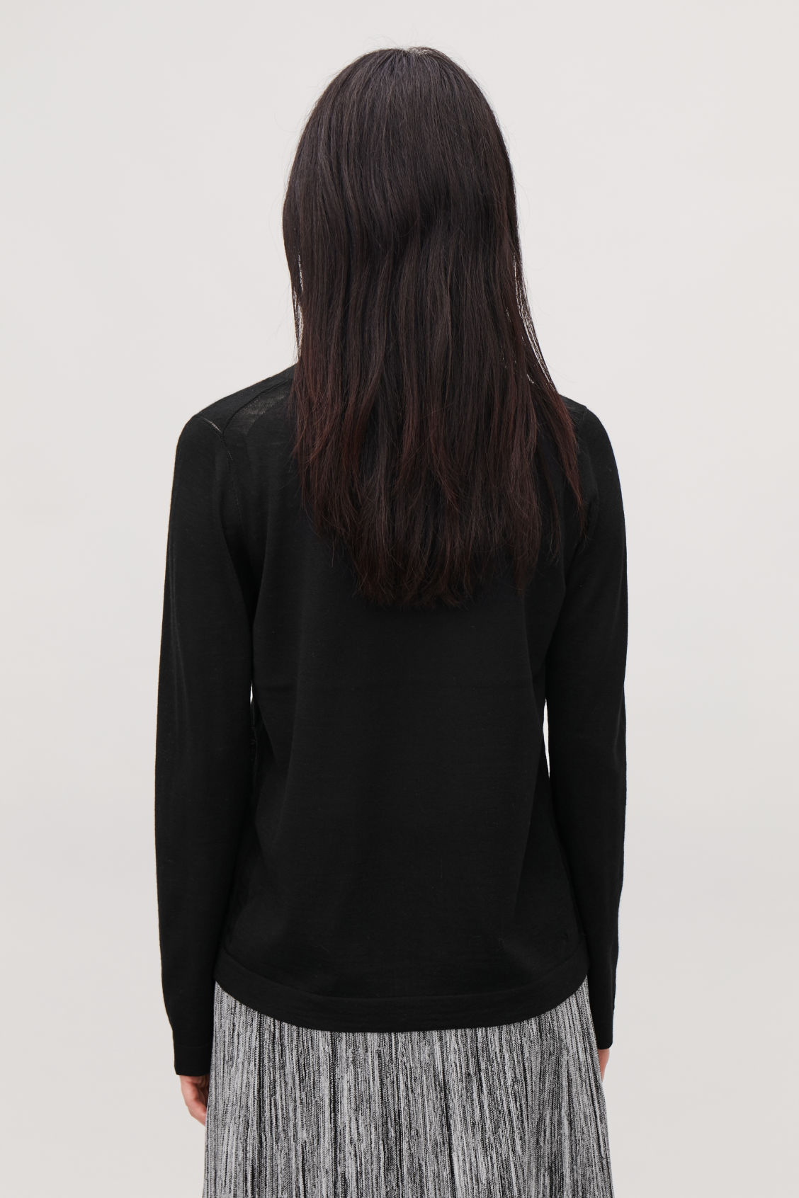 Model side image of Cos merino jumper with deep v-neck in black