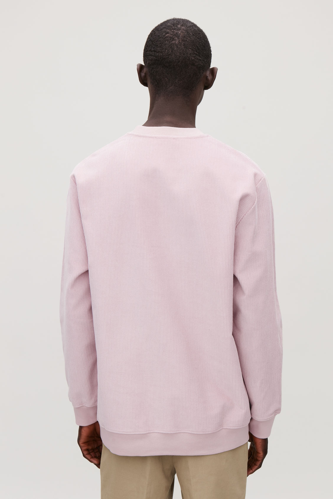 Model side image of Cos corduroy sweatshirt in pink
